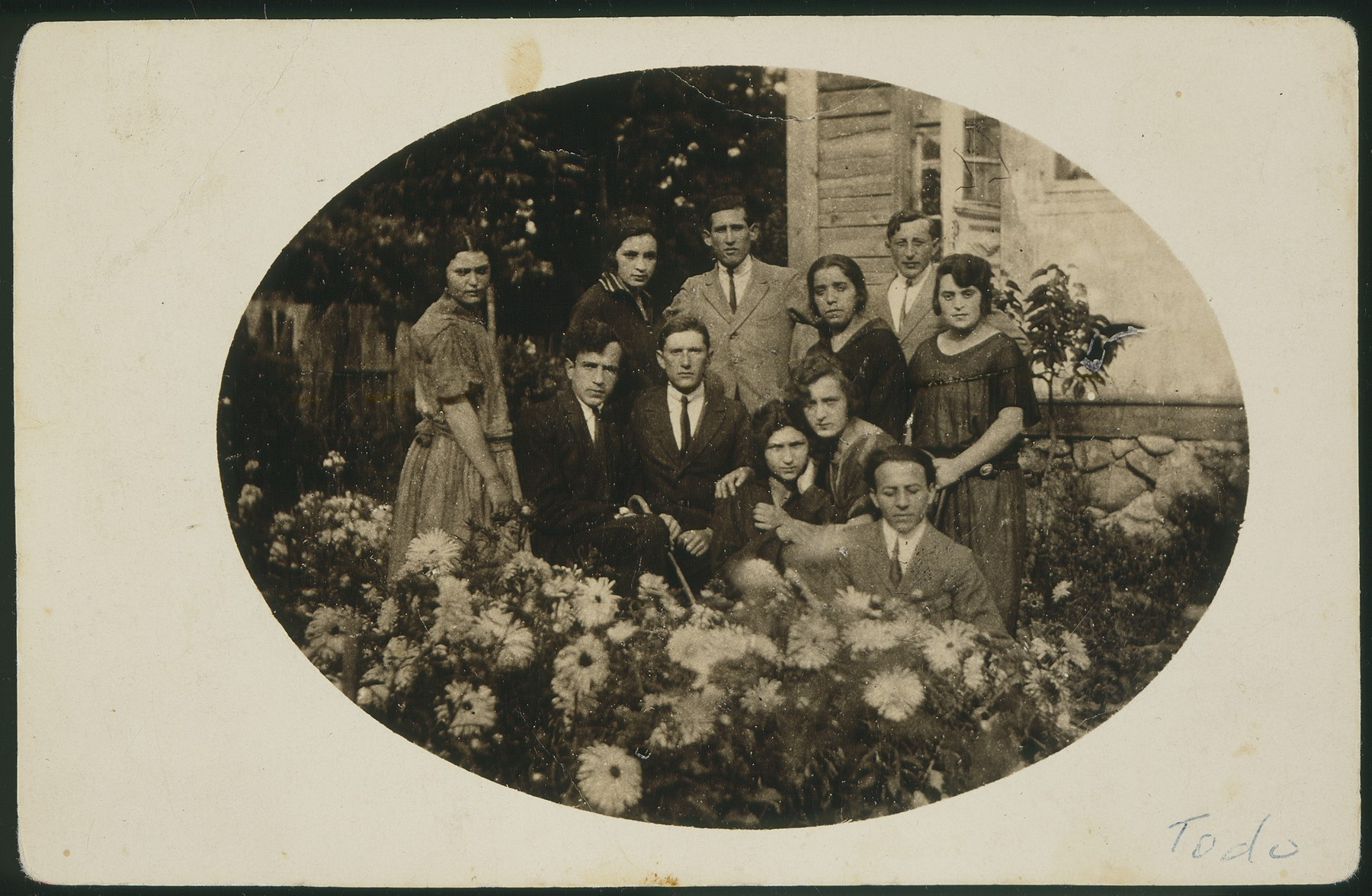 """Dora Zlotnik Berkowicz gathers in a garden with friends in honor of some of their forthcoming immigration to Palestine.  The photo is inscriberd with the following words:  """"The last minutes in Vasilishok.  Not always are words sufficient.""""  Dora also immigrated to Palestine a few years later."""