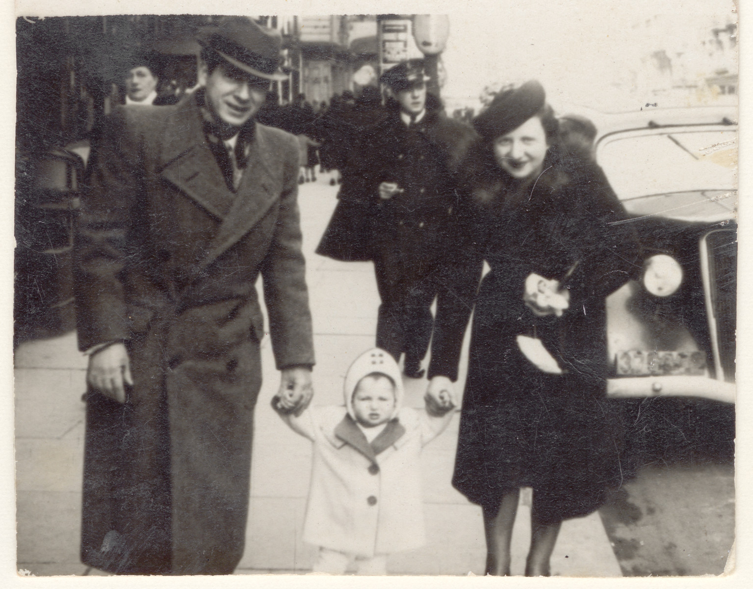 A Jewish family walks down the street hand in hand.  Pictured are Jacques and Fajga Aizenberg with their daughter, Josiane.