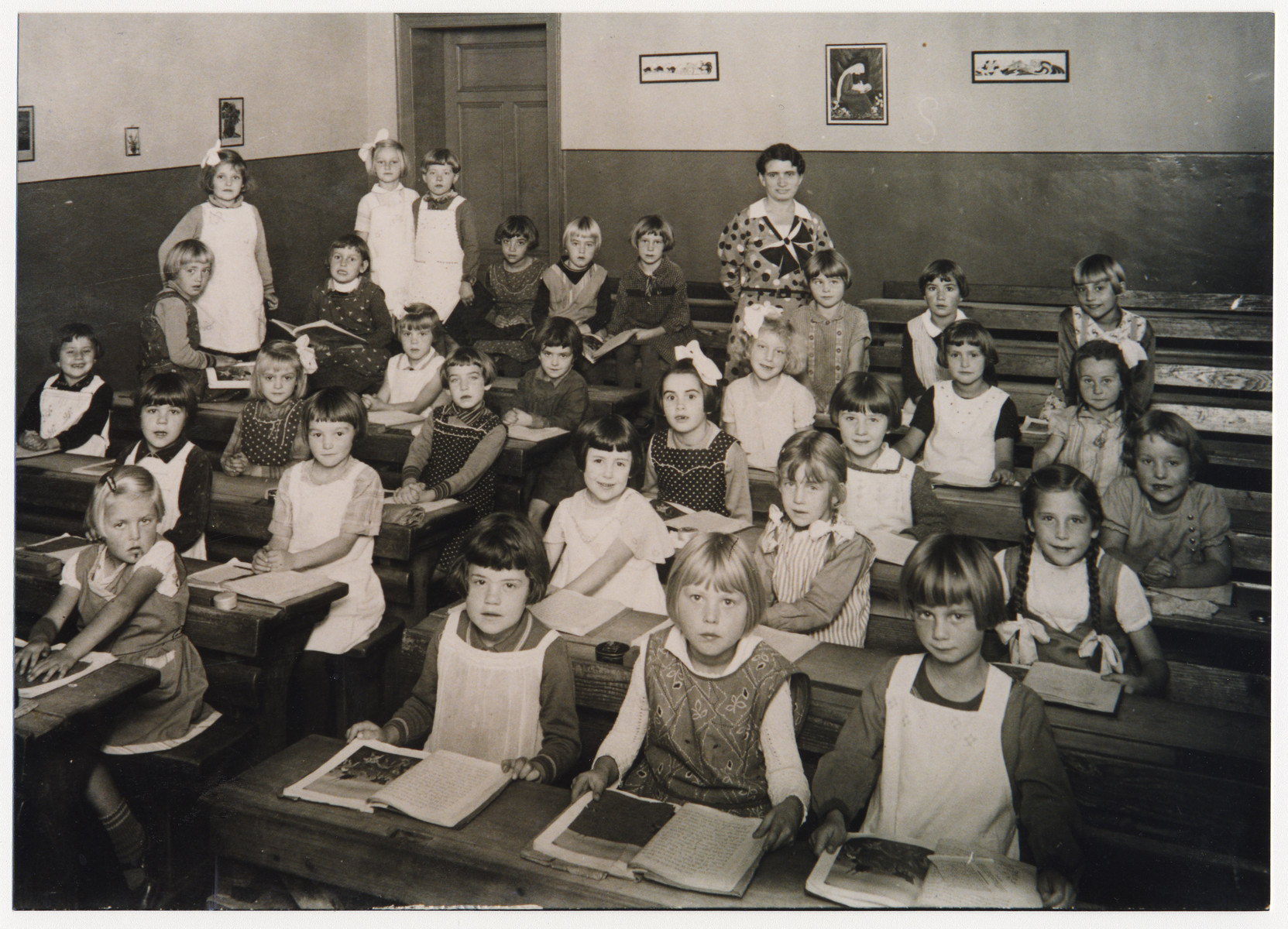 Group portrait of elementary school students seated at their desks.  Among those pictured (front row, second from the left) is .Ilse Kohnn, a cousin of the donor (Kurt Pauly).