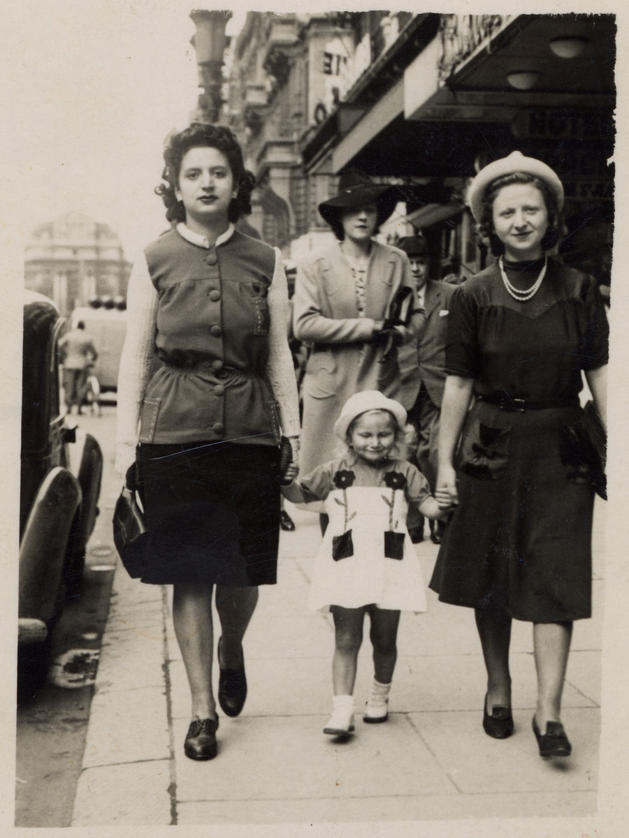 A Jewish family walks down the street hand in hand.  Pictured are Fajga Aizenberg (right), her sister, Rose Orenbuch, and daughter, Josiane.