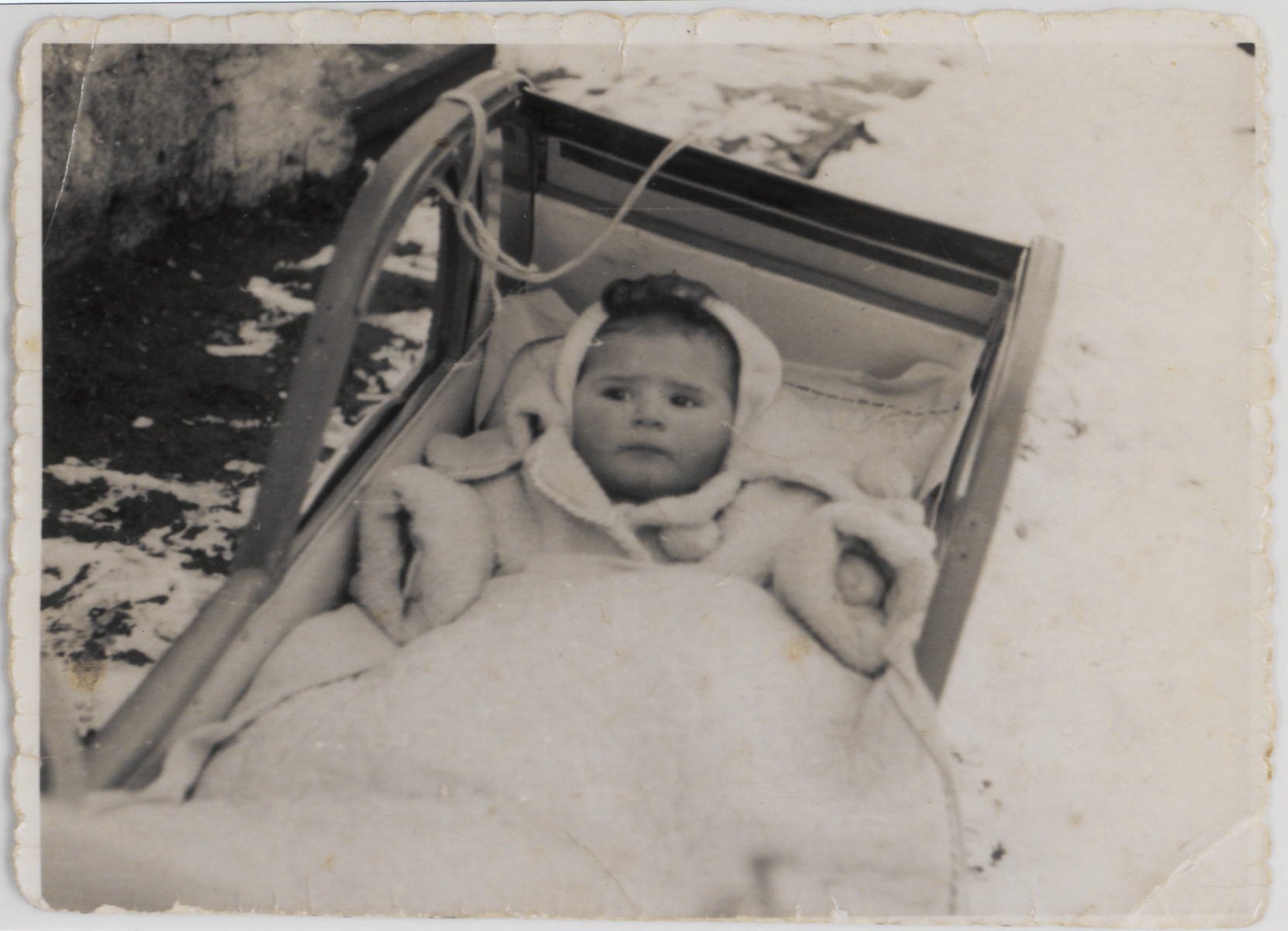 Portrait of a baby in a stroller, outside on a snowy day.  Pictured is Elizabeth Strassburger.