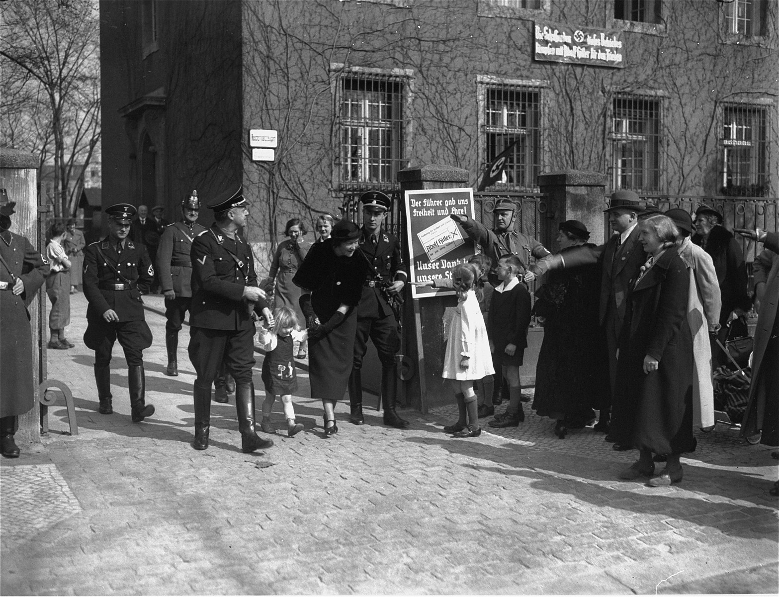 A member of the SA snaps a salute as Nazi Foreign Minister Joachim von Ribbentrop, accompanied by his wife and daughter, exits a polling place where he has just cast his vote.