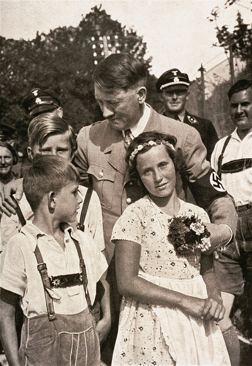 """Adolf Hitler poses with three children during an election campaign trip.    Also pictured is Baldur von Schirach (at the far right).  The original caption reads: """"One always sees the Fuehrer surrounded by children in pictures.""""  The young girl pictured has been identified as Christie Matthaei."""