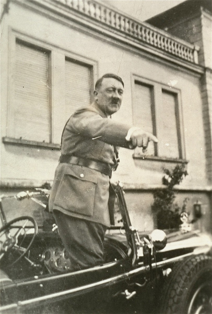 Hitler points at something while standing in his car [during an official procession].