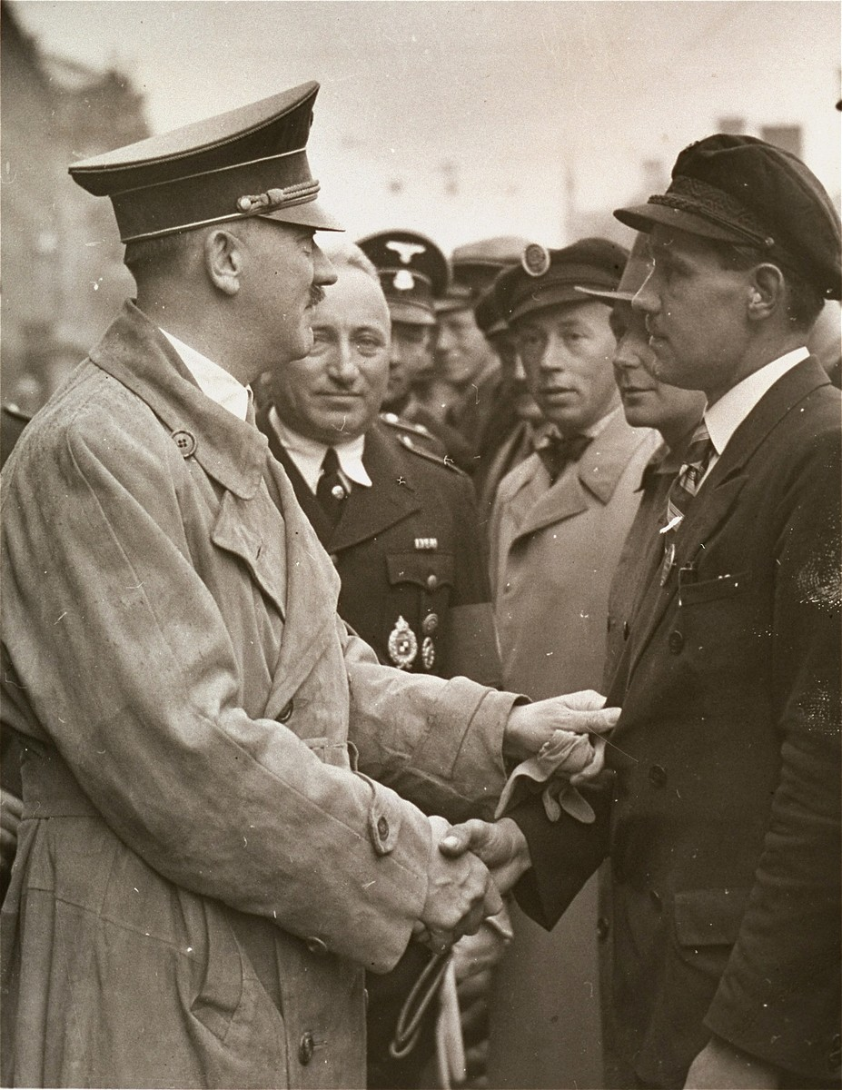 Adolf Hitler greets an autobahn worker at a Reichsparteitag (Reich Party Day) rally in Nuremberg.  Pictured second from the left is Robert Ley.