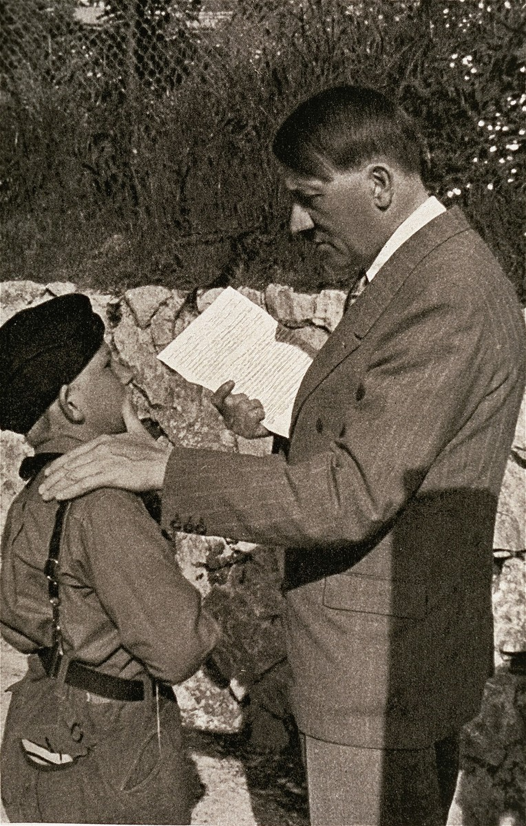 "A ""wolf-cub"" or junior member of the Hitler Youth hands Hitler a letter written by the child's sick mother."