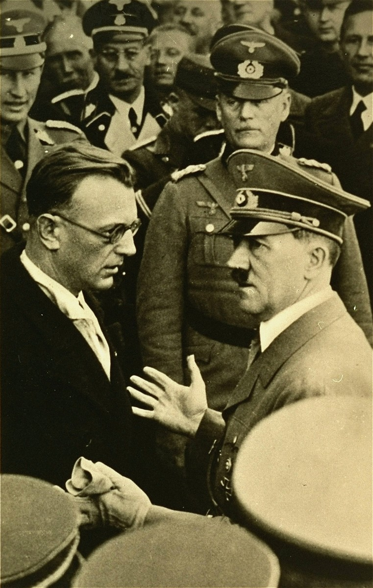 Hitler in conversation with Artur Seyss-Inquart (left) at an official ceremony.  Reinhard Heydrich stands behind Inquart (left), and General Wilhelm Keitel stands behind Hitler.