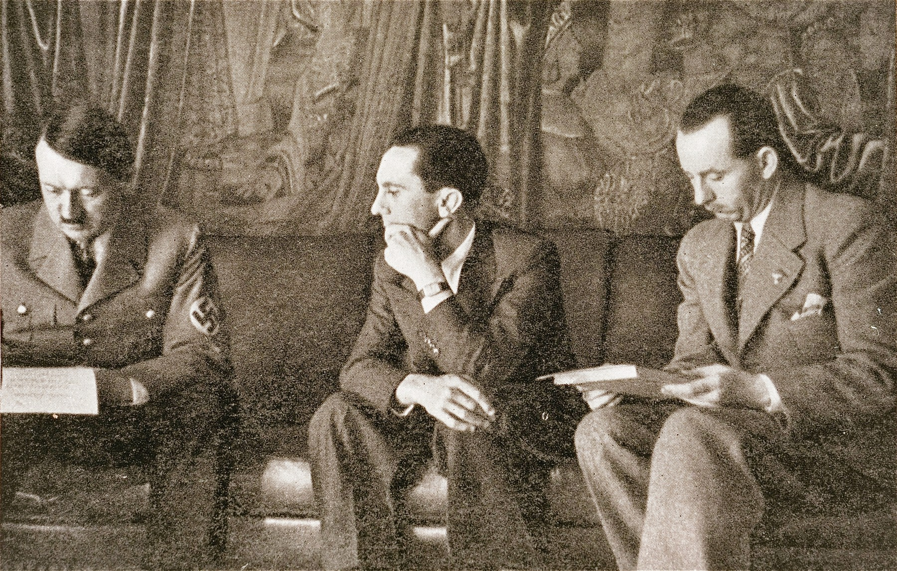 Minister of Propaganda Joseph Goebbels waits while Adolf Hitler reviews a document in the chancellery.