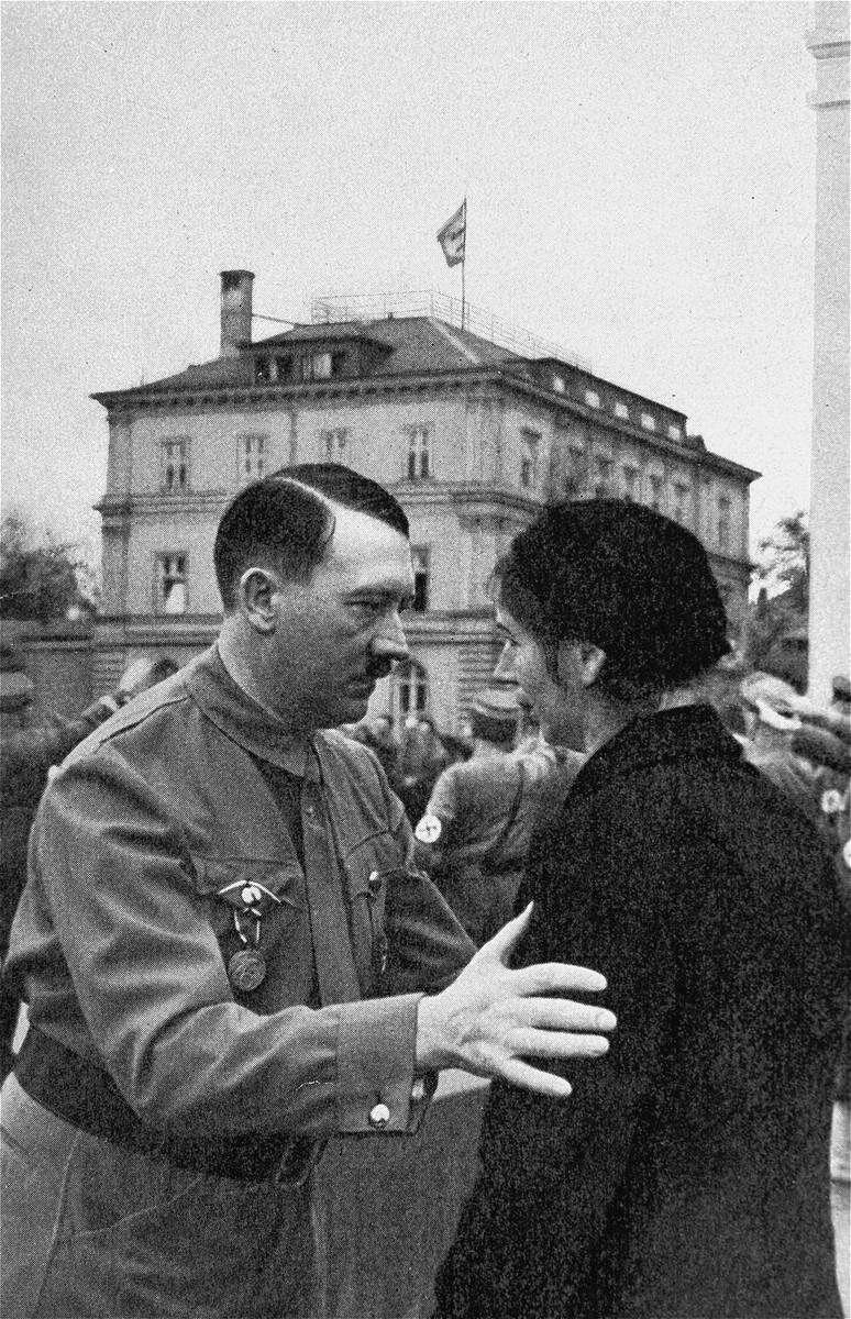 Adolf Hitler speaks to the widow of a Nazi party member who died during the 1923 Beer Hall Putsch.  In the background is the Brown House.