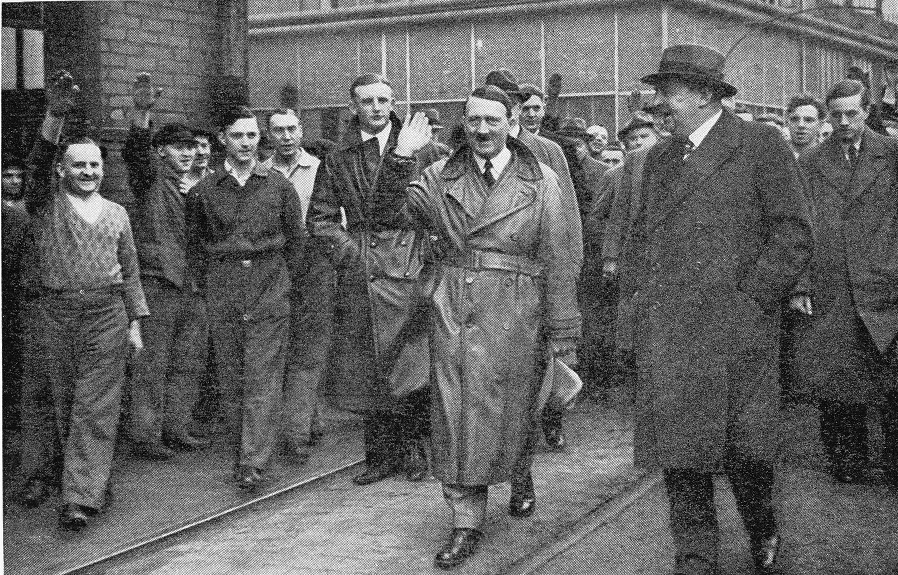 Adolf Hitler salutes a crowd of workers during a tour of industries in Rhineland-Westphalia.