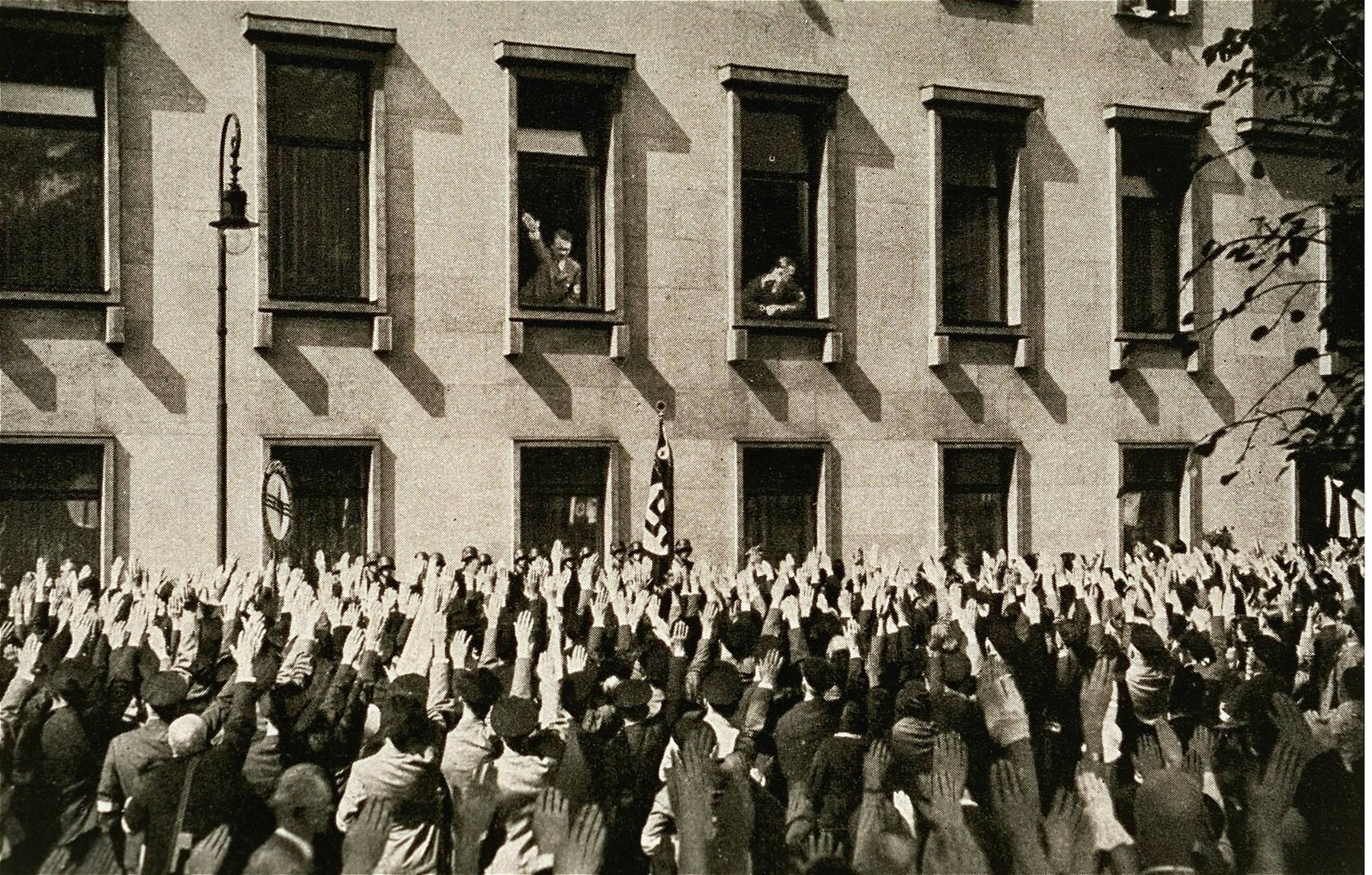 A delegation from the Saar region salutes Hitler from the street in front of the chancellery building.