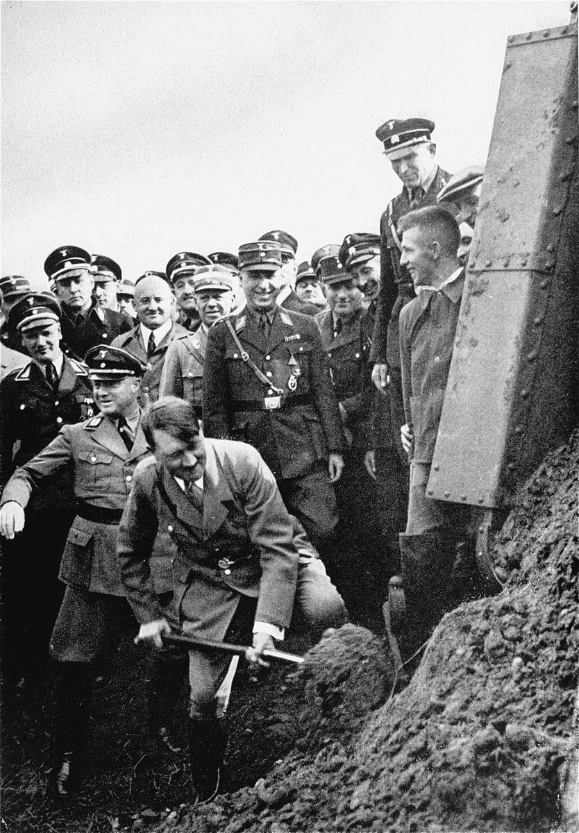 Adolf Hitler inaugurates the construction of a stretch of the Autobahn by turning over the first shovelful of earth, as Nazi officials look on.