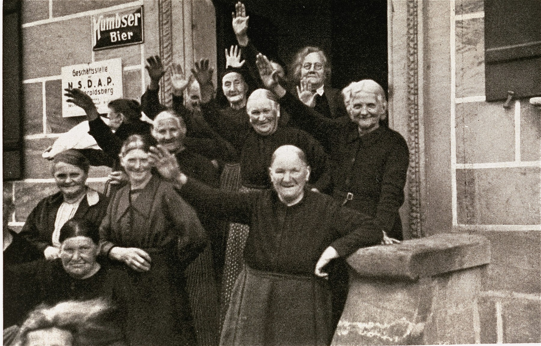 Women in a small village wave and salute Hitler's passing Motorcade.