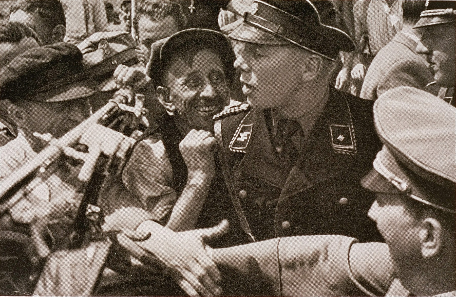 An SS guard shields Adolf Hitler from enthusiastic supporters who wish to shake his hand.