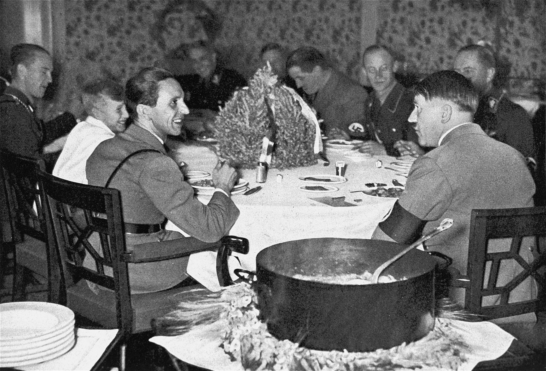 """Adolf Hitler and Joseph Goebbels share a meal on """"Eintopf Sonntag.""""    One Sunday a month, Germans ate a one-pot meal and contributed the savings to public charities.  The pot is in the foreground."""