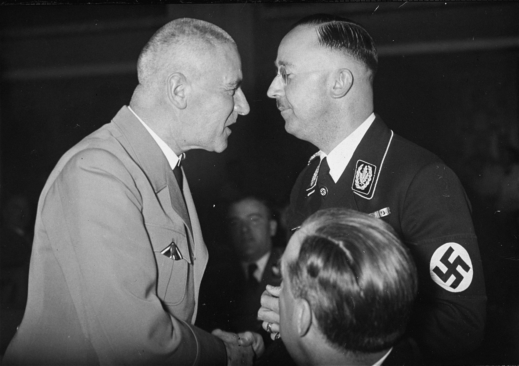 "Reichsminister of the Interior Wilhelm Frick greets Heinrich Himmler at a ""Friendship Evening"" for Reichstag delegates."