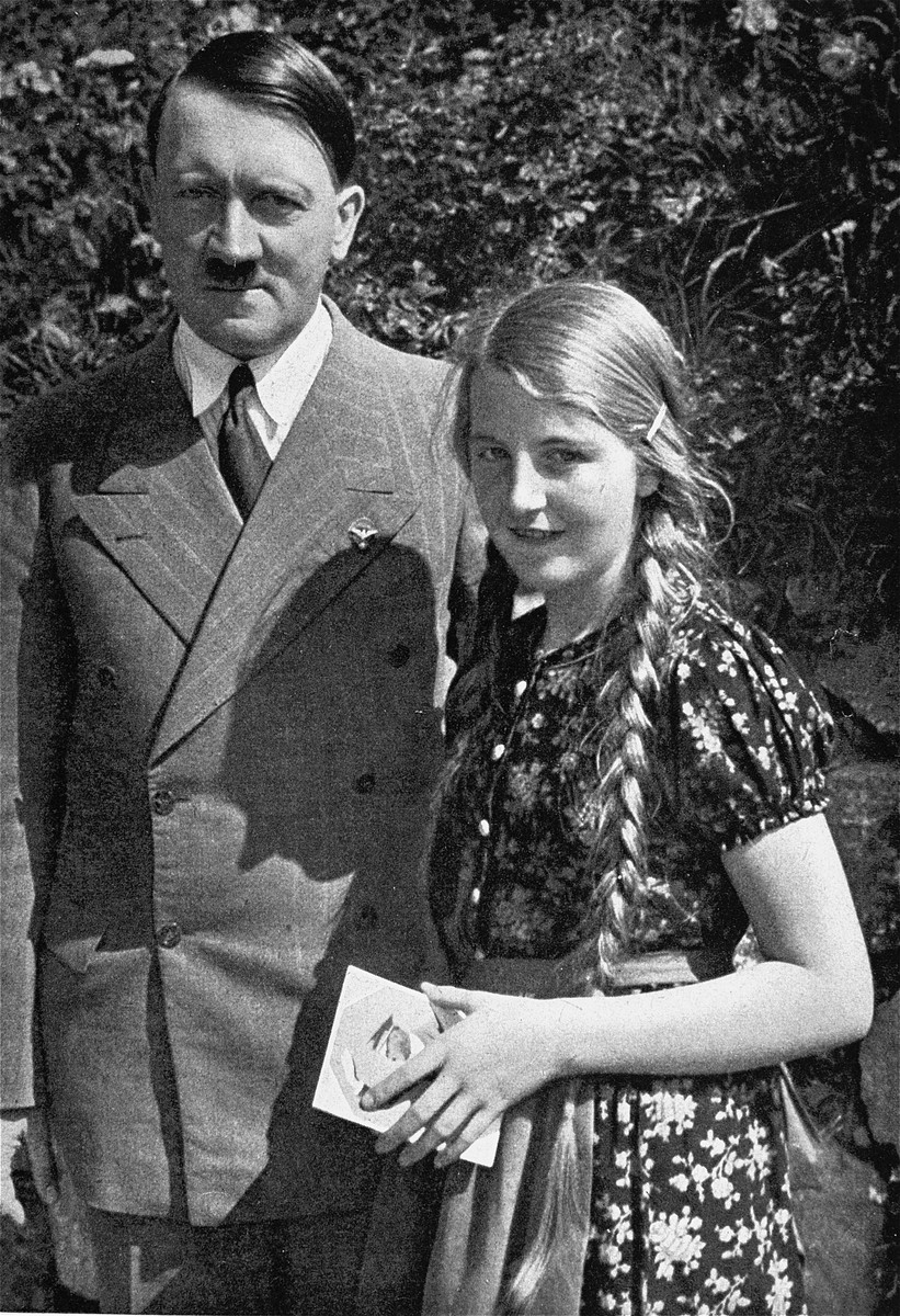 Adolf Hitler poses with a young girl, to whom he has given his autograph.