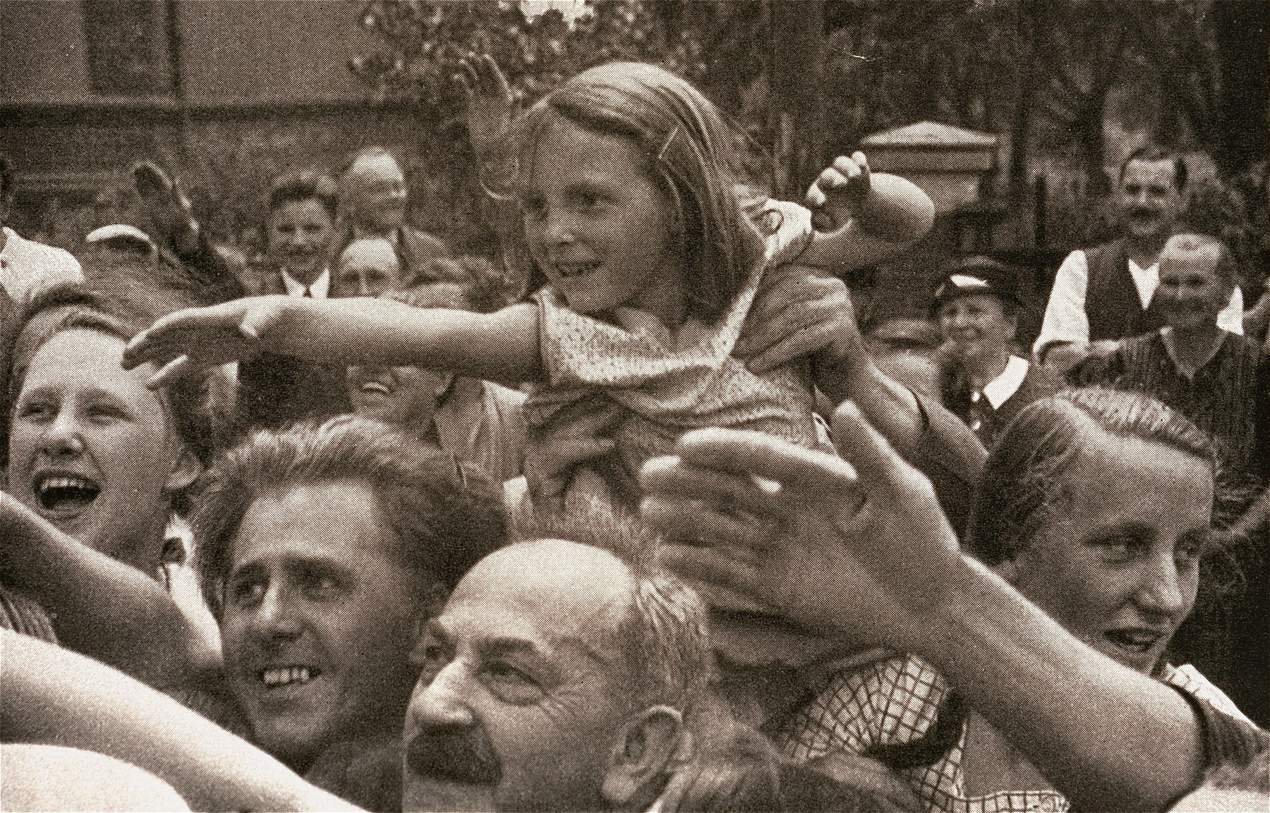 A girl reaches out to Adolf Hitler as he leaves the building site of the House of German Art in Munich.