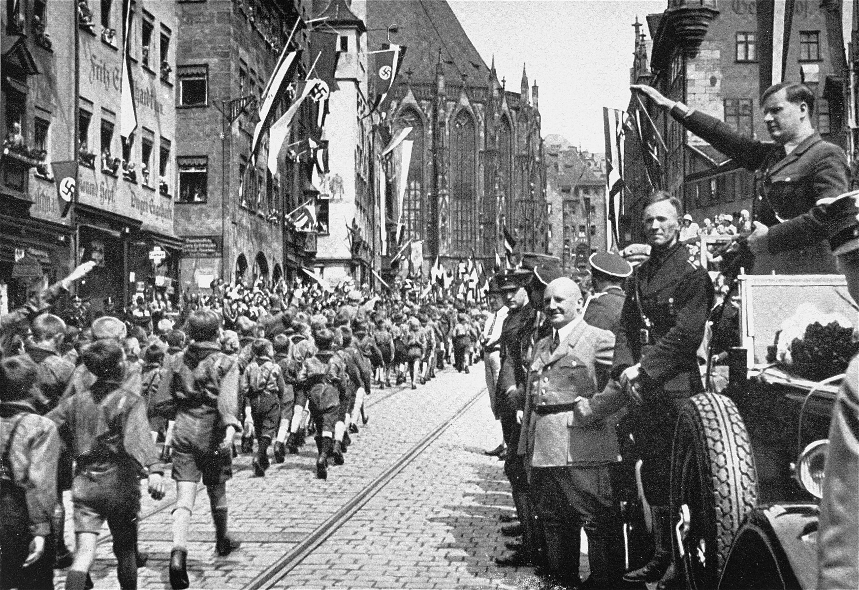 """Baldur von Schirach (saluting), leader of the Hitler Youth, and Julius Streicher (in light-colored jacket), editor of the antisemitic newspaper, """"Der Stuermer,"""" review a parade of Hitler Youth in Nuremberg."""