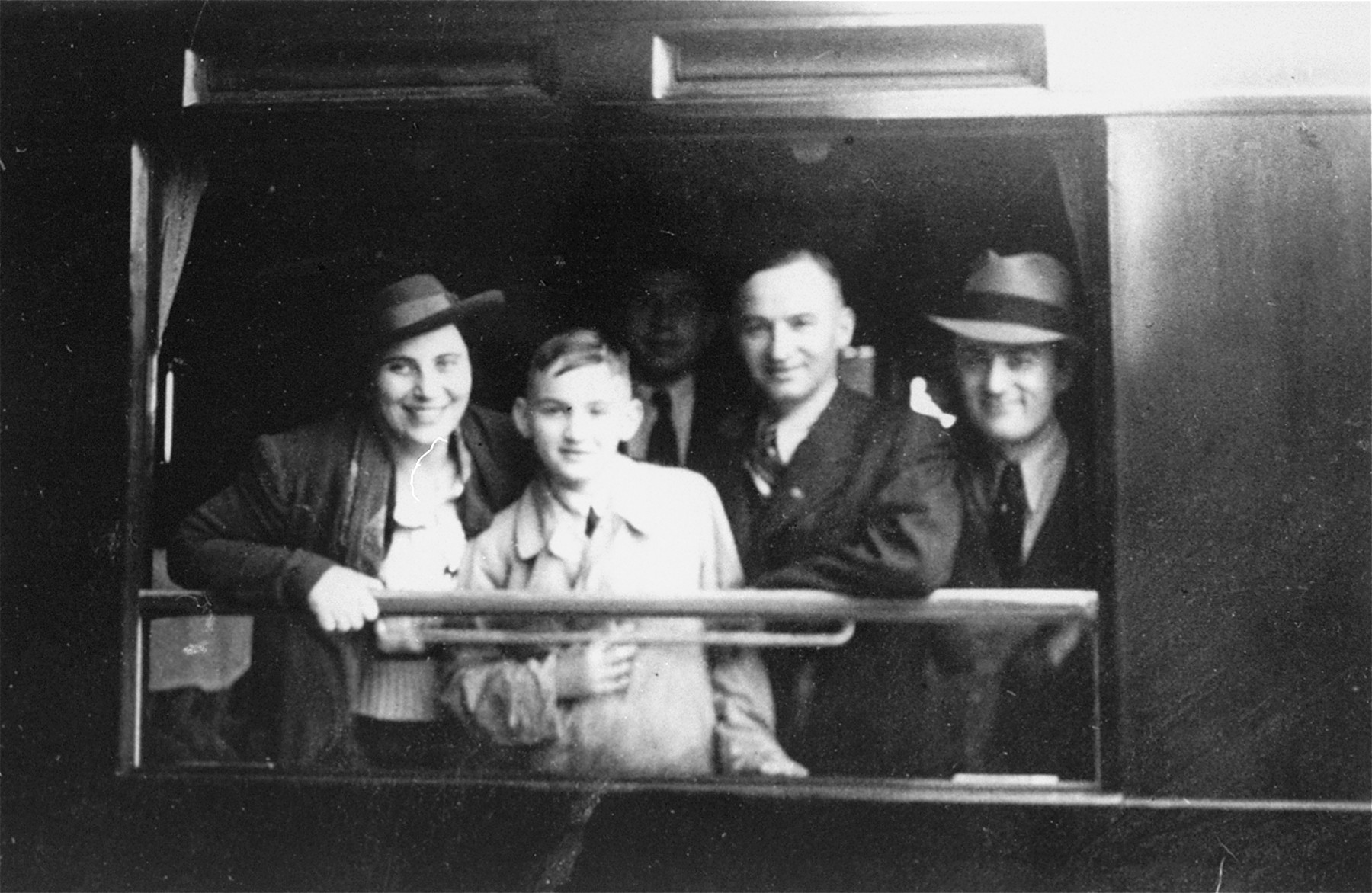 A Jewish family poses at the window of their railcar before the train leaves the station.  The family is leaving Germany for the United States.  Pictured are Sol and Henrietta Meyer with their son Harvey.  The Meyers are the aunt and uncle of the donor, Jill Berg Pauly,