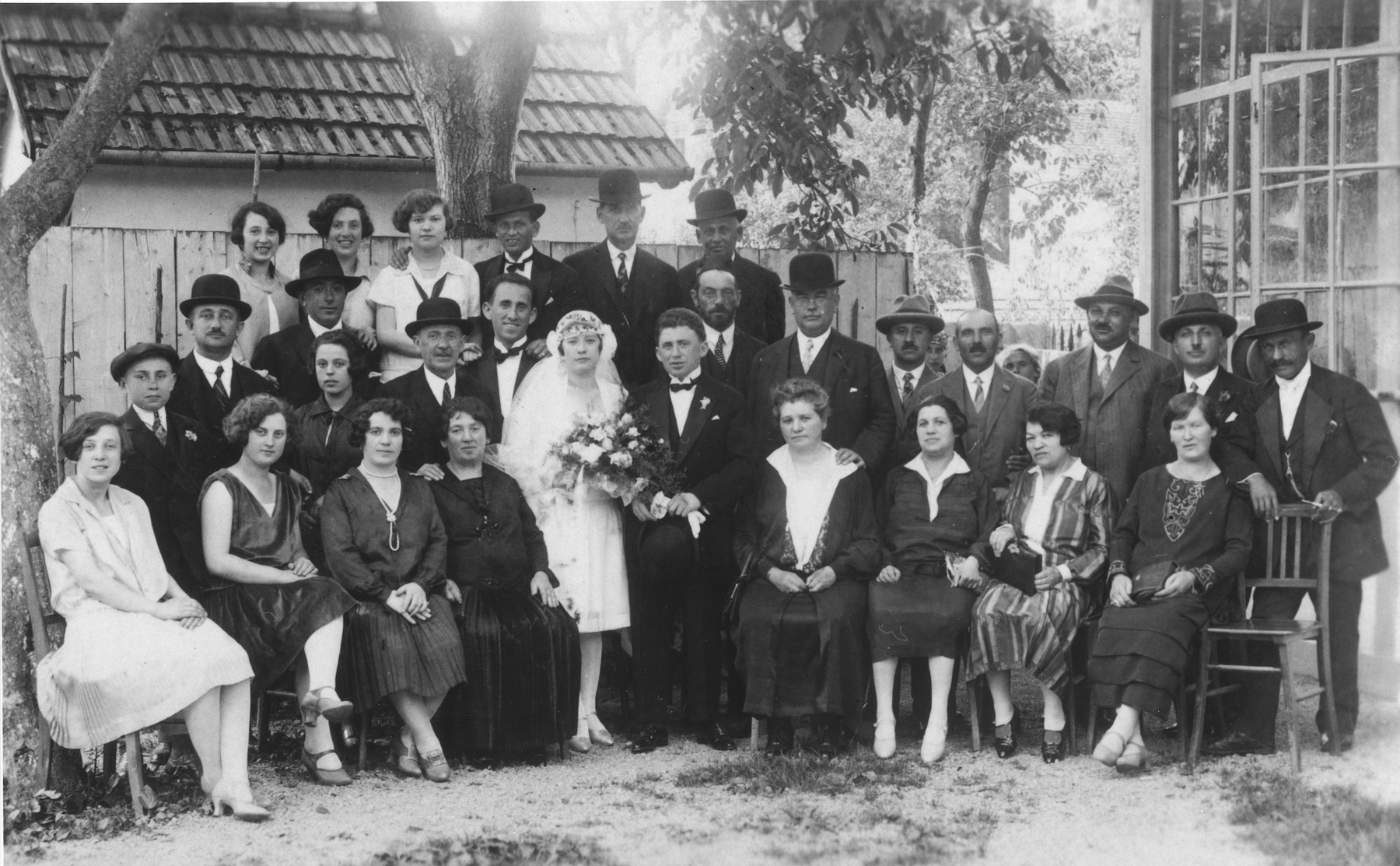 Portrait of an extended Jewish family at a wedding in Galanta, Slovakia.  The bride and groom are Ilona Pressburger and Natan Beck.  Pictured from left to right.  Front row: Olga Beck, Margit Beck, Etelka Beck, Cecilia Reiss Beck, Ilona Pressburger, Natan Beck, Fani Lowinger Pressburger and others unknown.  Second row: Irvin Beck, Michael Binetter, unknown, Jakub Beck, Bela Beck, unknown, Max Mordechai, others unknown.  Top row: Manci Beck, Frederika Beck, Elisheva Pressburger and others unknown.