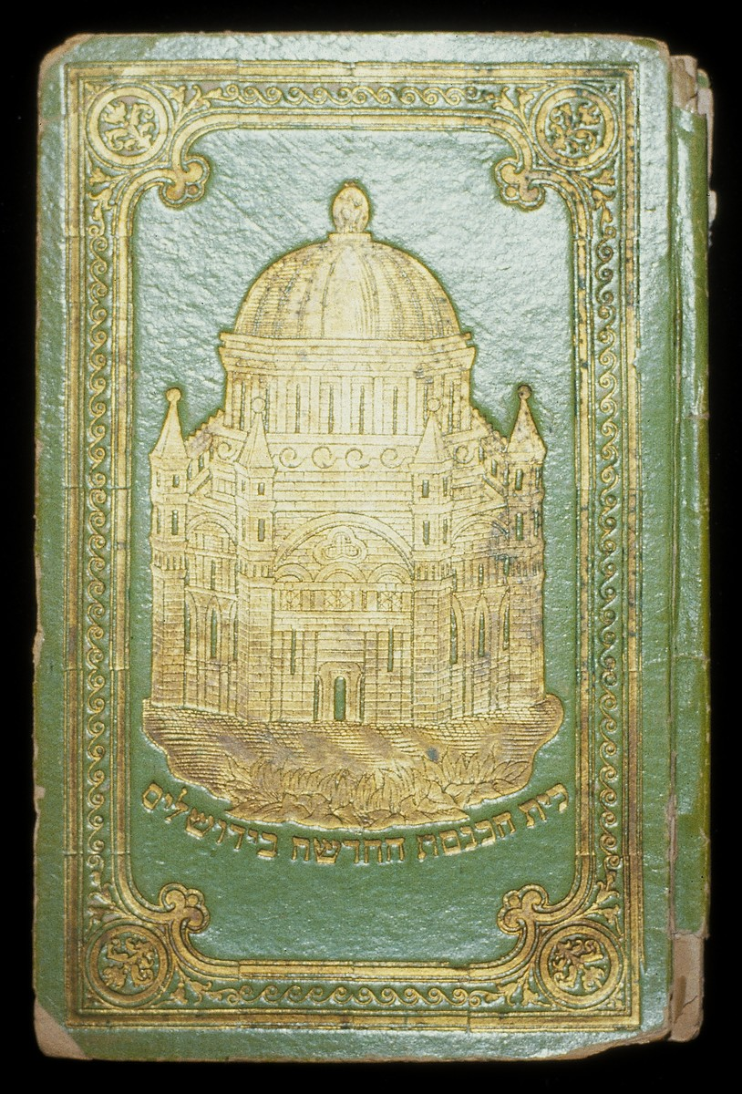 "Front cover of a Haggadah with an image of a temple, painted in gold.  The Hebrew lettering reads, ""The new synagogue in Jerusalem"".  The Haggadah has a bright green cover with gold decoration and lettering."
