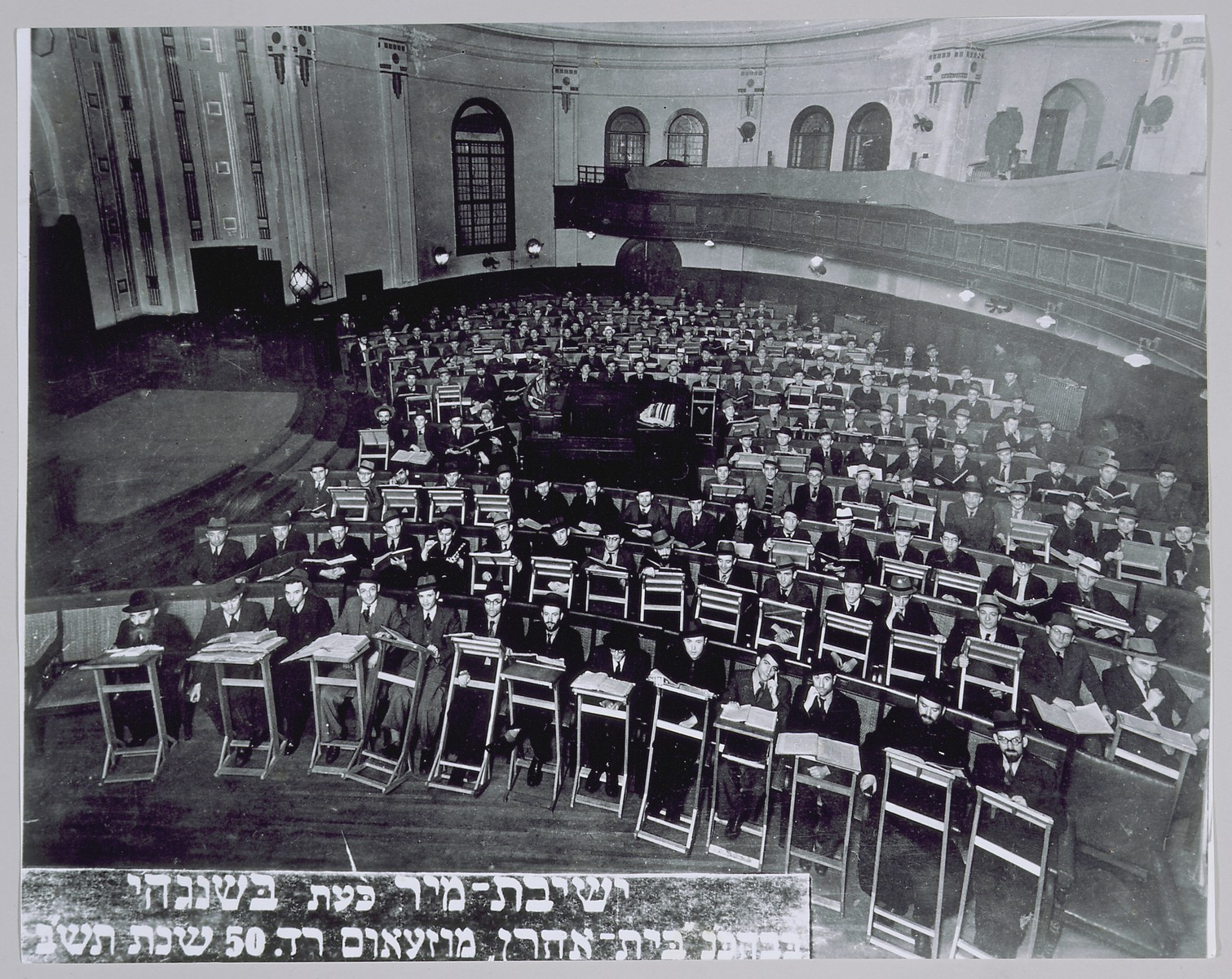 Students and teachers of the exiled Mir yeshiva study in the sanctuary of the Beth Aharon synagogue on Museum Road in Shanghai.  Among those pictured are: Rabbi Chezkel Lewensztejn (front row, first from the left); Rabbi Chaim L. Szmuelowicz, acting dean (front row, second from the right); and Rabbi J.D. Epstein, secretary (front row, first from the right).