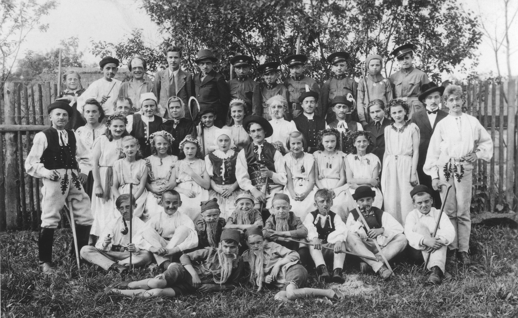 Group portrait of children and teachers at the Myjava public school dressed up in costumes.  Among those pictured is Magdalena Beck (third row from the front, third from the left).
