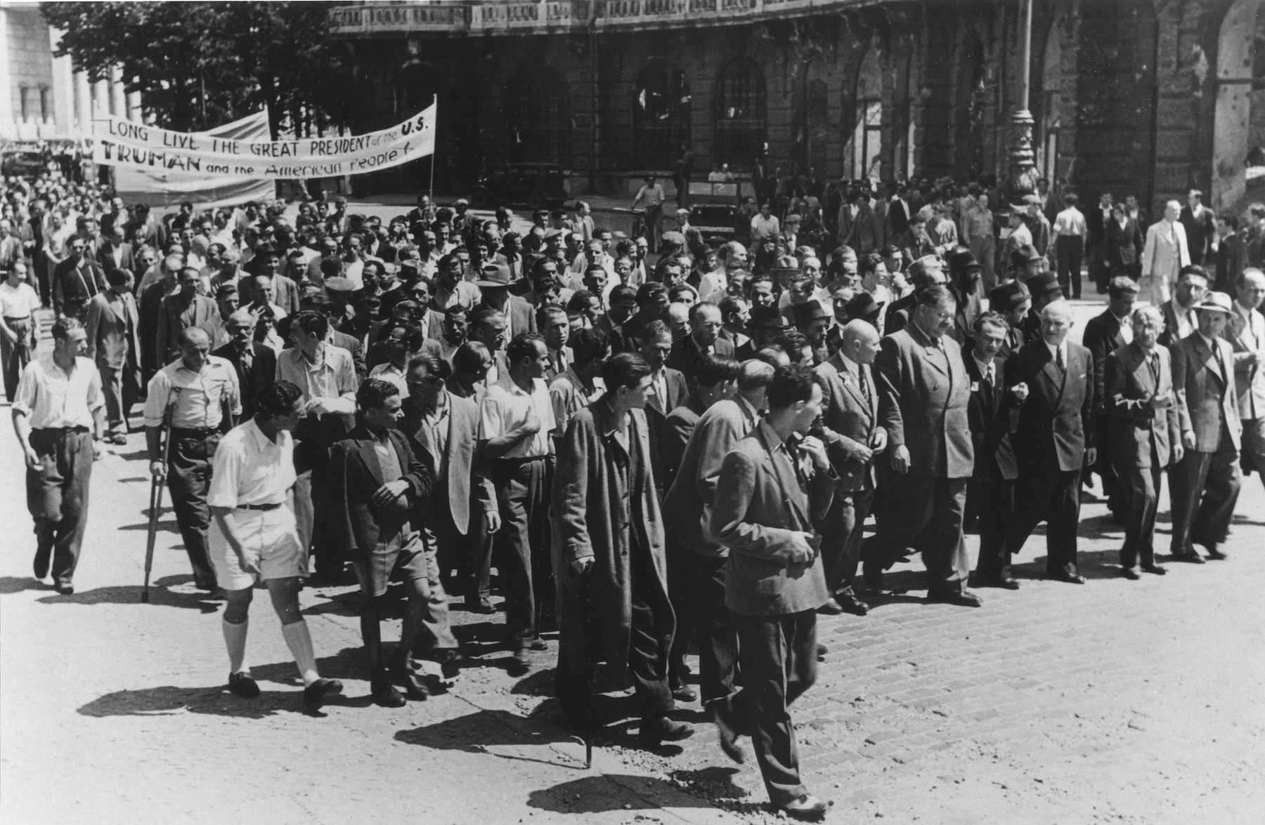"Jewish DPs march beneath a banner that reads ""Long Live the Great President of the US Truman and the American People!""  Among those pictured is Philipp Auerbach (tall man marching in the front row, center)."