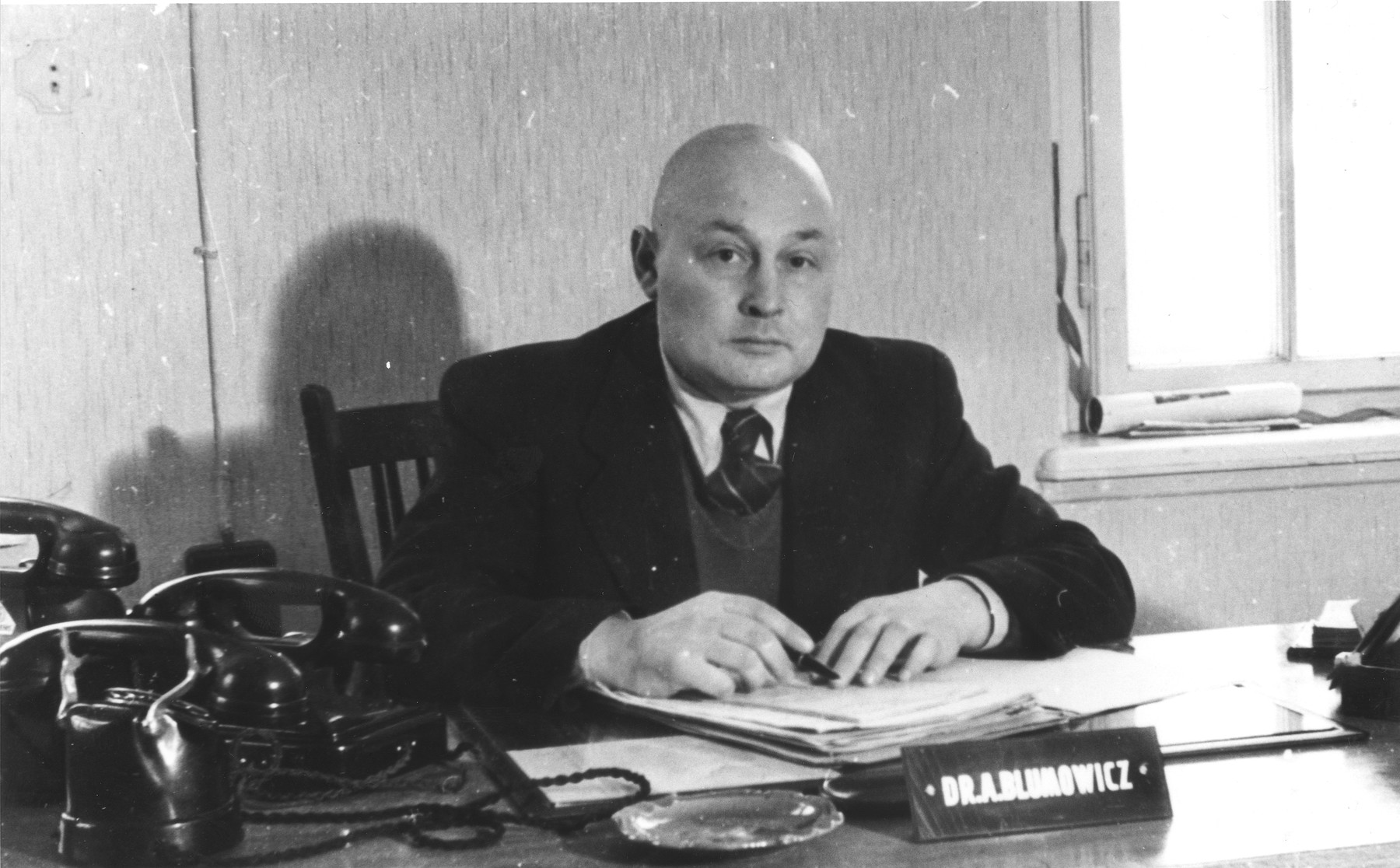 Portrait of Dr. Abrasha Blumowicz, a member of the executive of the Central Committee of Liberated Jews in the US Zone of Germany, seated at his desk.