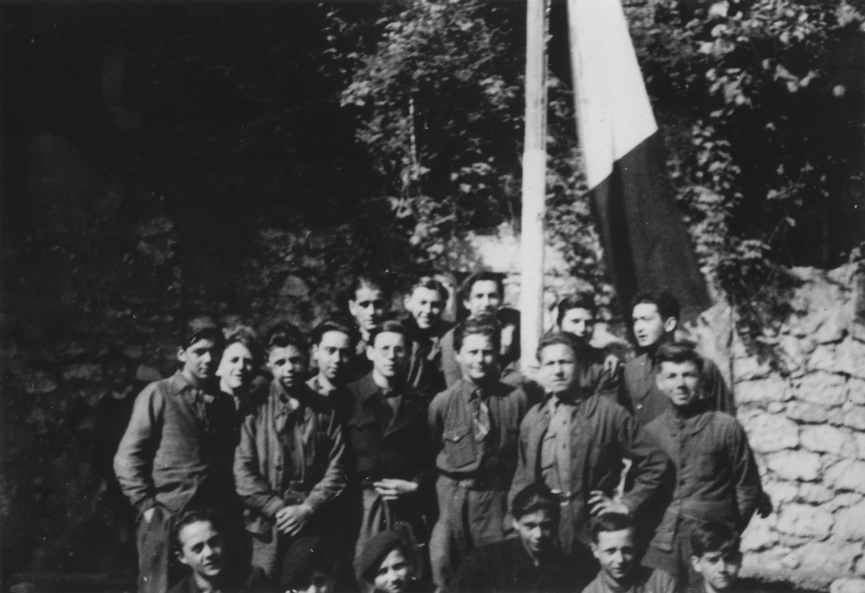 The members of the Vichy fascist youth movement, Moissons Nouvelles, gather around a flag pole in Pont de Beauvoisin.  A few of the boys are hidden Jews who were placed at the center by the OSE (Oeuvre de Secours aux Enfants).