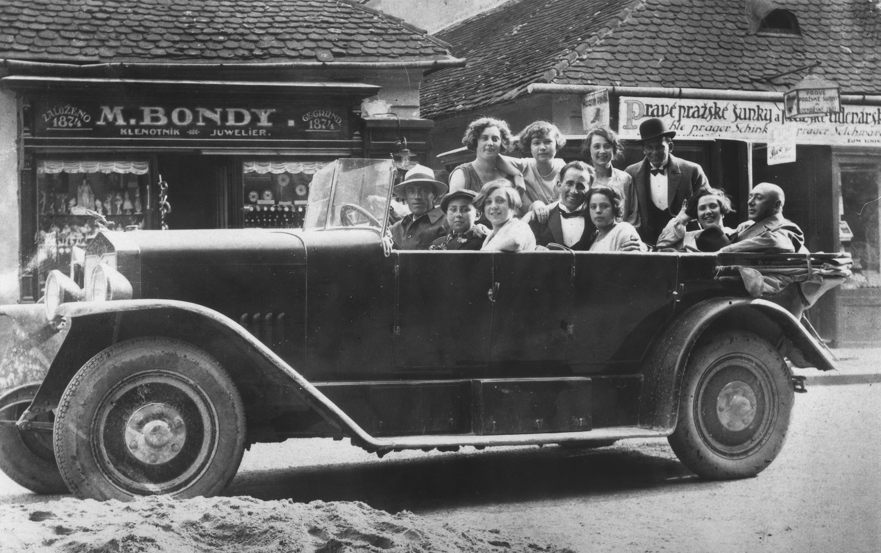 The Beck family goes for a ride in a large automobile.  Among those pictured are Margit, Erwin, Olga, Bela, Fredericka and Ilona Beck.