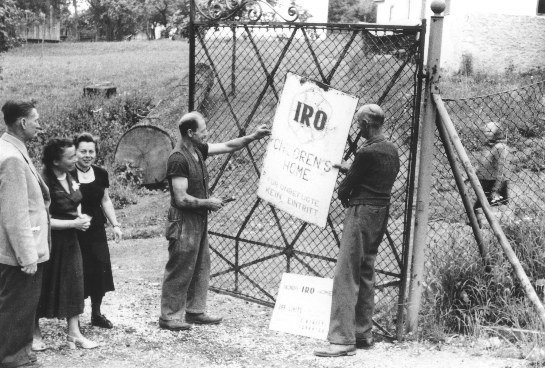 Workmen hang up a sign on the gate of the new IRO [International Refugee Organization] children's home in Leitendorf, Austria.