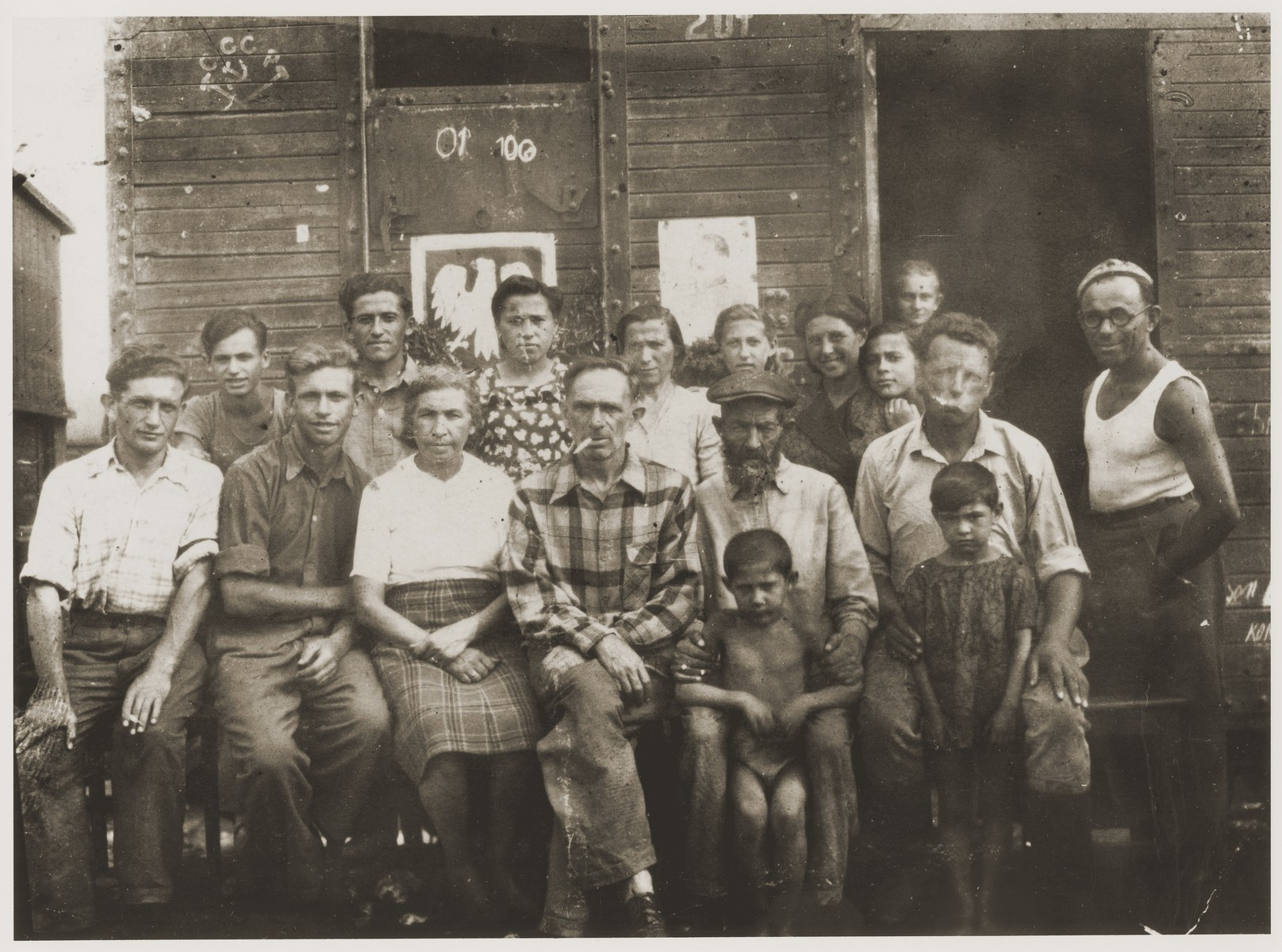Doba [Cymerman] Yermus, Moshe Yermus, (center) and their sons Sam (third from left) and Aaron (second from left) wait at a train station in Khazakstan for their return to Poland following the end of World War II.