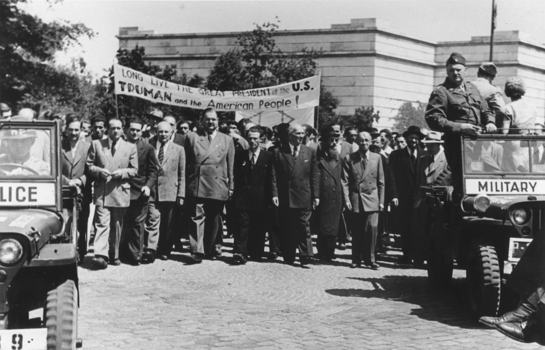 "Jewish DPs march beneath a banner that reads ""Long Live the Great President of the US Truman and the American People!""  Among those pictured is Philipp Auerbach (center)."