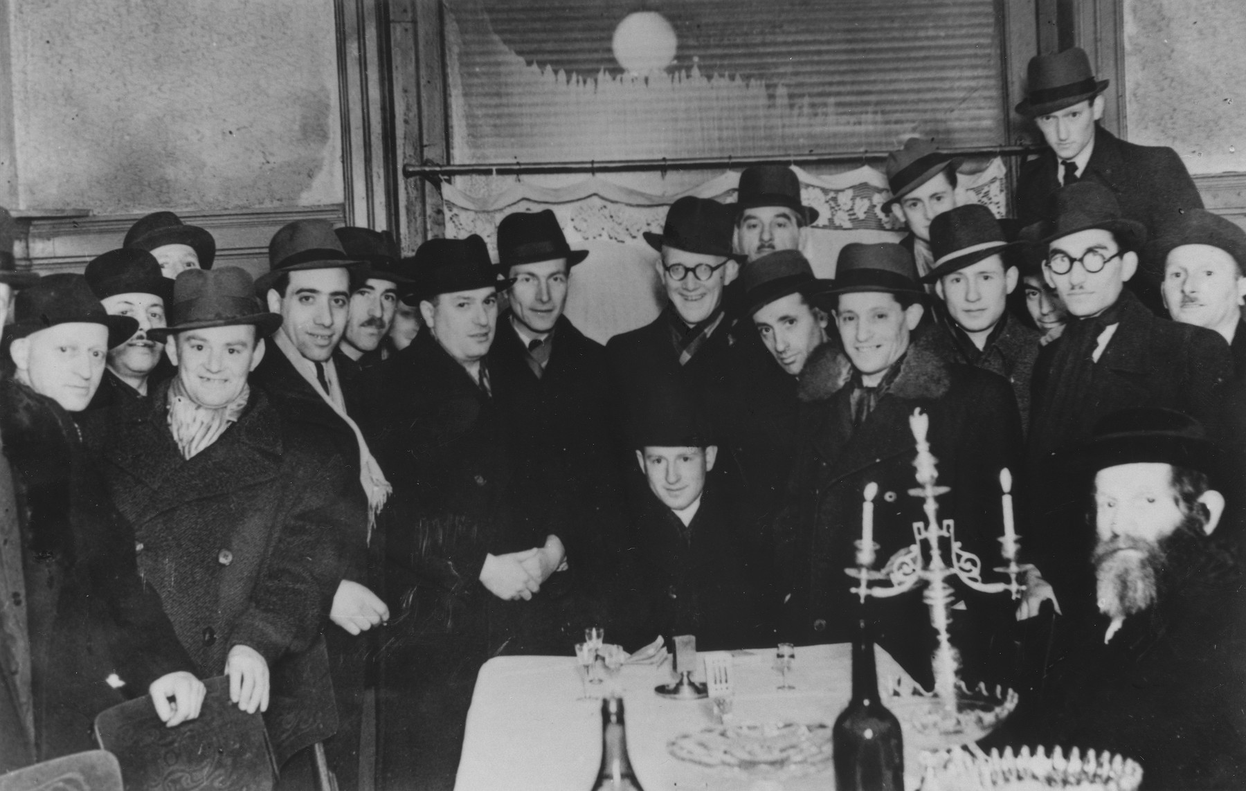 A group of men gather around Ernst Eizikowits to celebrate his wedding to Helena Friedmann.  All but two of those pictured perished.  Shortly after the wedding, Ernst was taken to the Sarospatak labor camp.  He was killed in 1943 at the age of 29.