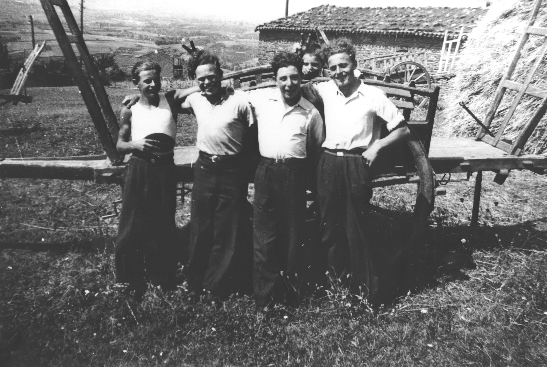 Jewish youth in hiding pose with other agricultural workers in front of a hay wagon on a farm in Treves.  Among those pictured is Julien Bluschtein (second from the right) and Herbert Karliner (third from the right).