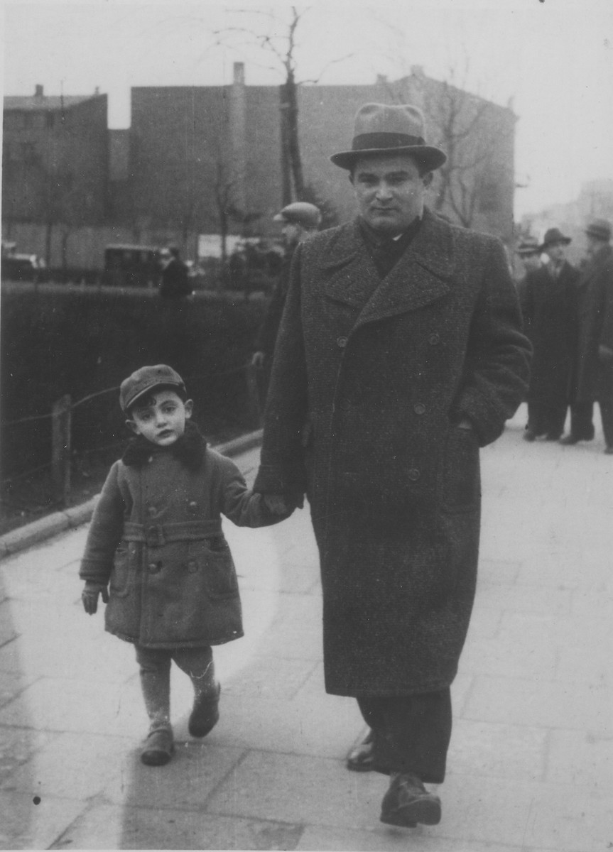 Itzhak Granek walks with his son Dawid along a street in Bedzin.