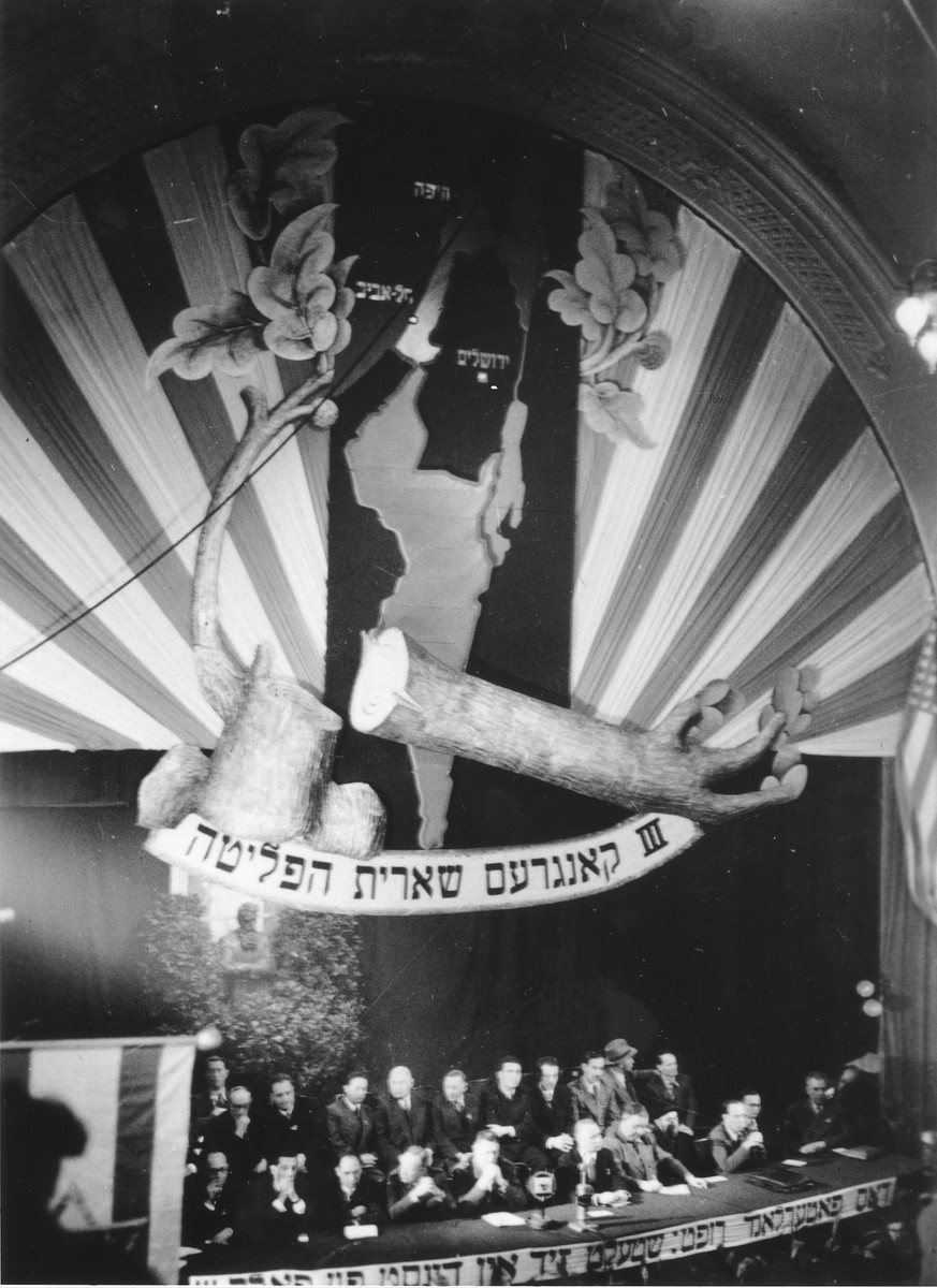 The emblem of the Surviving Remnant [Sheerit Hapletah] hangs above the dais at the Third Conference of Liberated Jews in the US Zone of Germany.    The emblem consists of a felled tree with a small branch growing from it superimposed upon a map of Palestine.