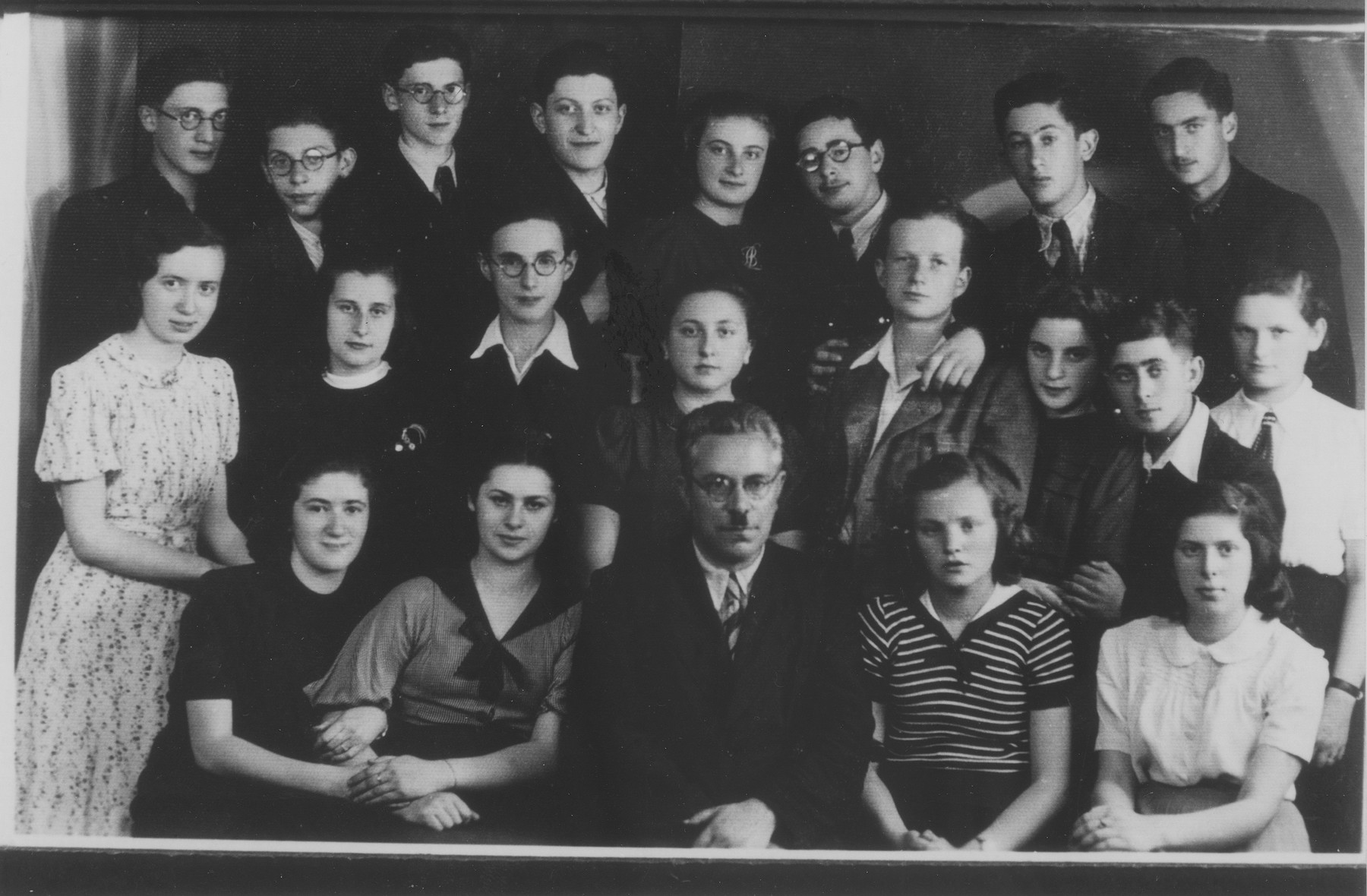 Prof. Elster poses with his students at the Furstenberg Gymnasium in Bedzin.  Seated in the front row, from left to right are: Lola Lustiger; Genia Szpigelman; Prof. Elster; Rozka Feder; Franka Grundman.  Second row: Renia Nunberg; Gucia Slowatycka; Mendek Rechnic; Sala Goldberg; Heniek Blumenfrucht; Bela Ehrlich; Izio Koenigsberg; Golda Grynberg. Third row: Izak Blumenkranc; Natek Buchner; Samek Zelinger; Zabner; Lola Brodkiewicz; Moniek Teitelbaum; unknown; and Jerzyk Mandelkern.