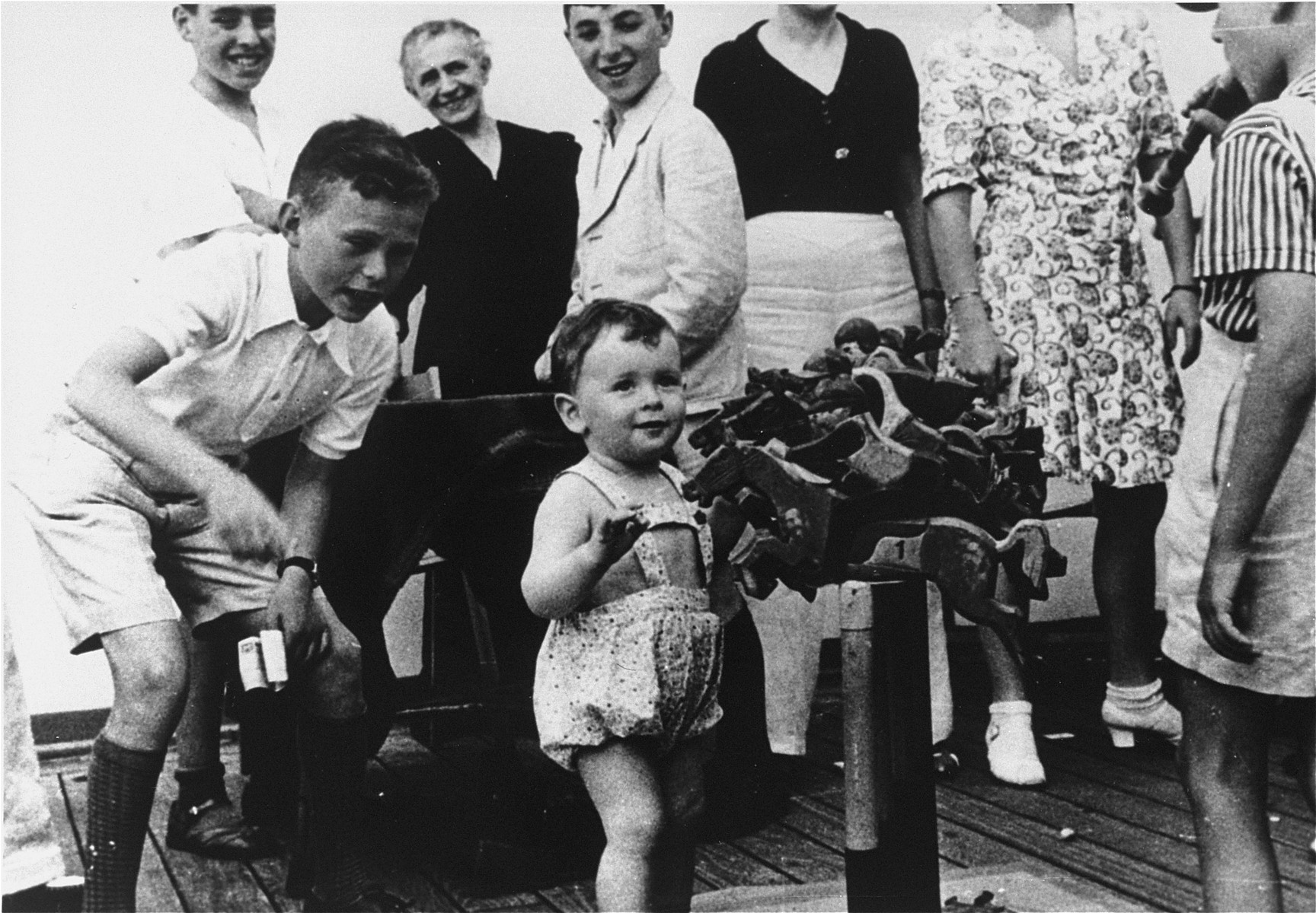 Heiner Vendig (center) plays with a steeplechase toy on the deck of the MS St. Louis.  Herbert Karliner is pictured standing behind him at the left.