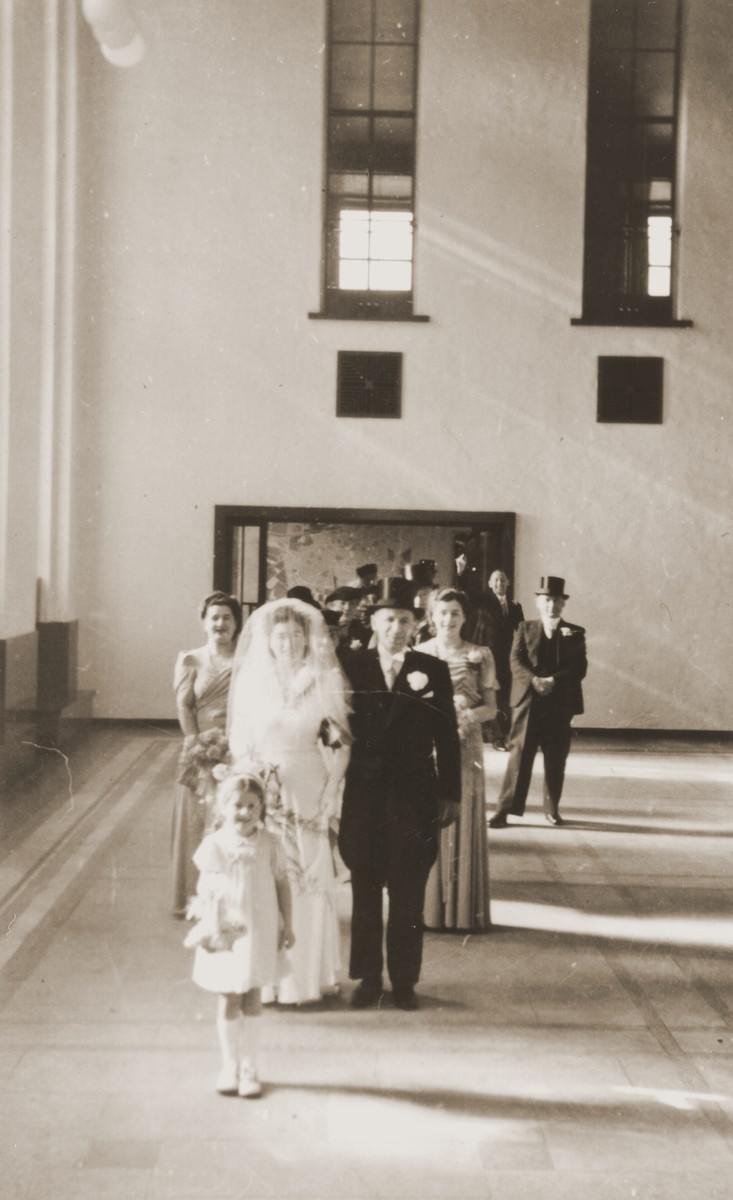 The wedding of Julius Jacob Zion to Nora de Jong at the synagogue in Enschede.  Also pictured are Wilhelmina Esther Zion, Julius' sister (behind the bride); Mientje de Jong, Nora's sister (behind the groom); and Betty Rosenbaum, the flower girl, who is Julius' niece.  Betty, who lost both her parents during the war, was adopted by Julius and Nora after their marriage.