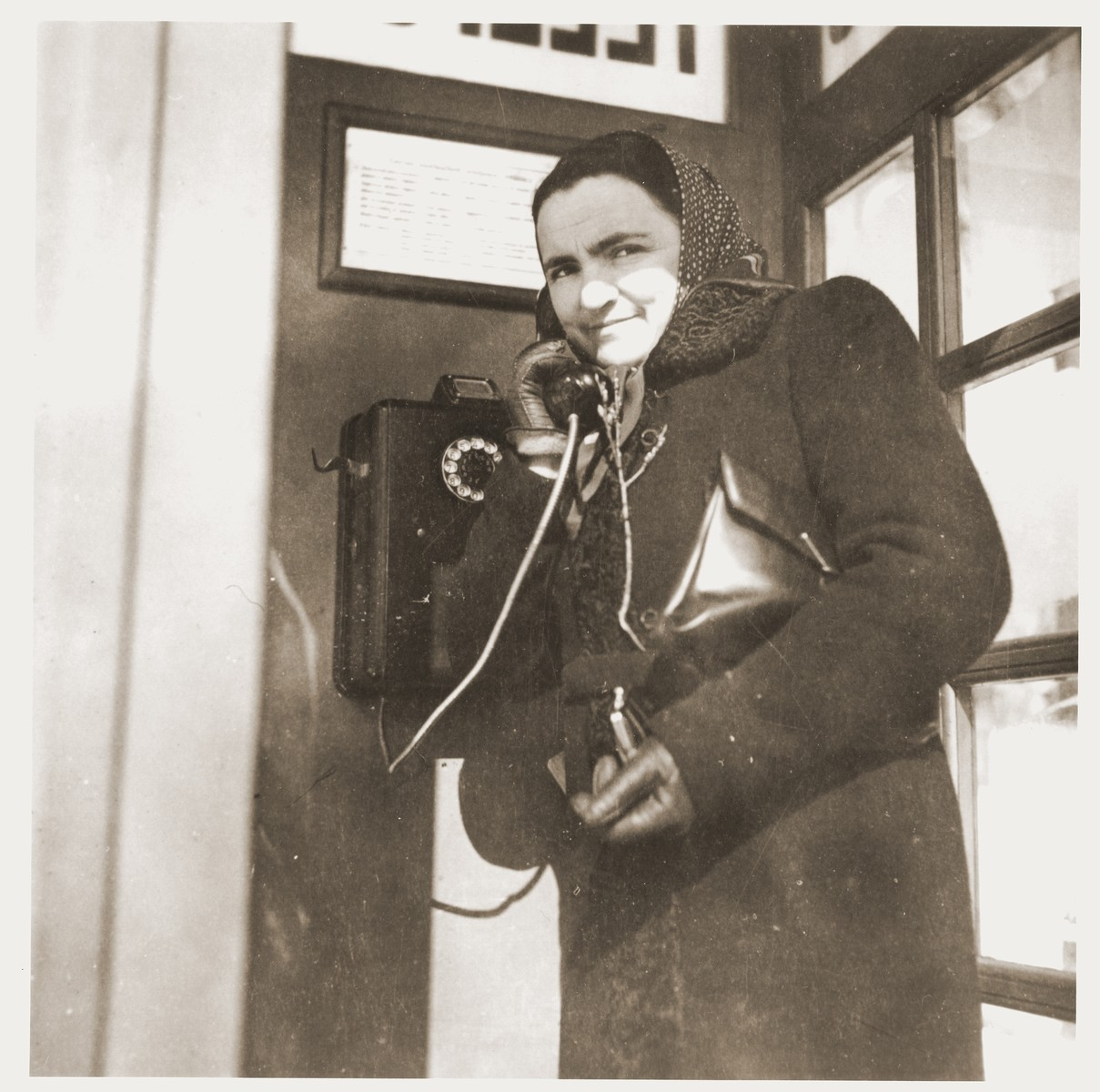 Shulamit Rabinovitch standing in one of the few public telephone booths in downtown Kaunas.
