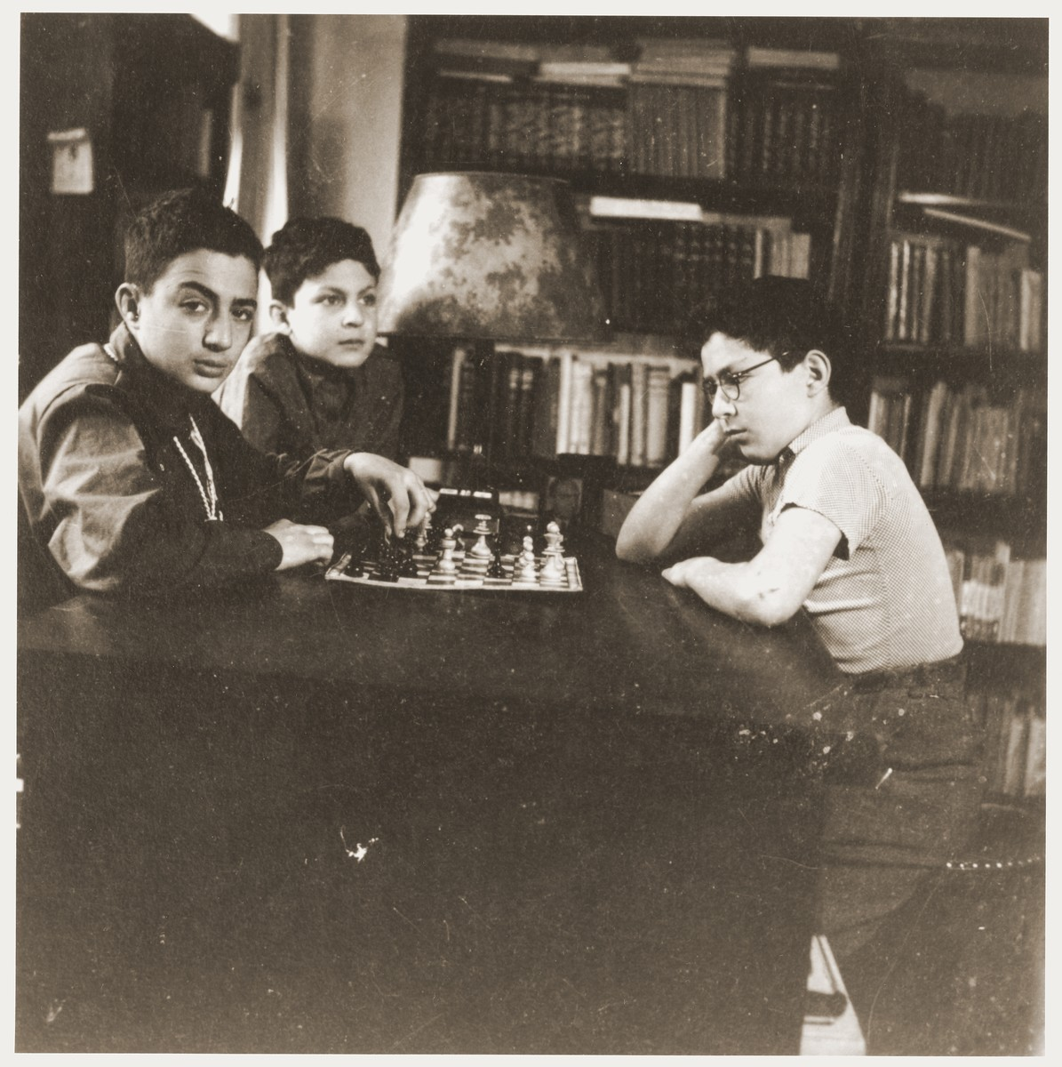 Amos and Binyamin Rabinovitch playing chess in the family house on Gedimino Street.  Their younger brother Shmuel looks on.