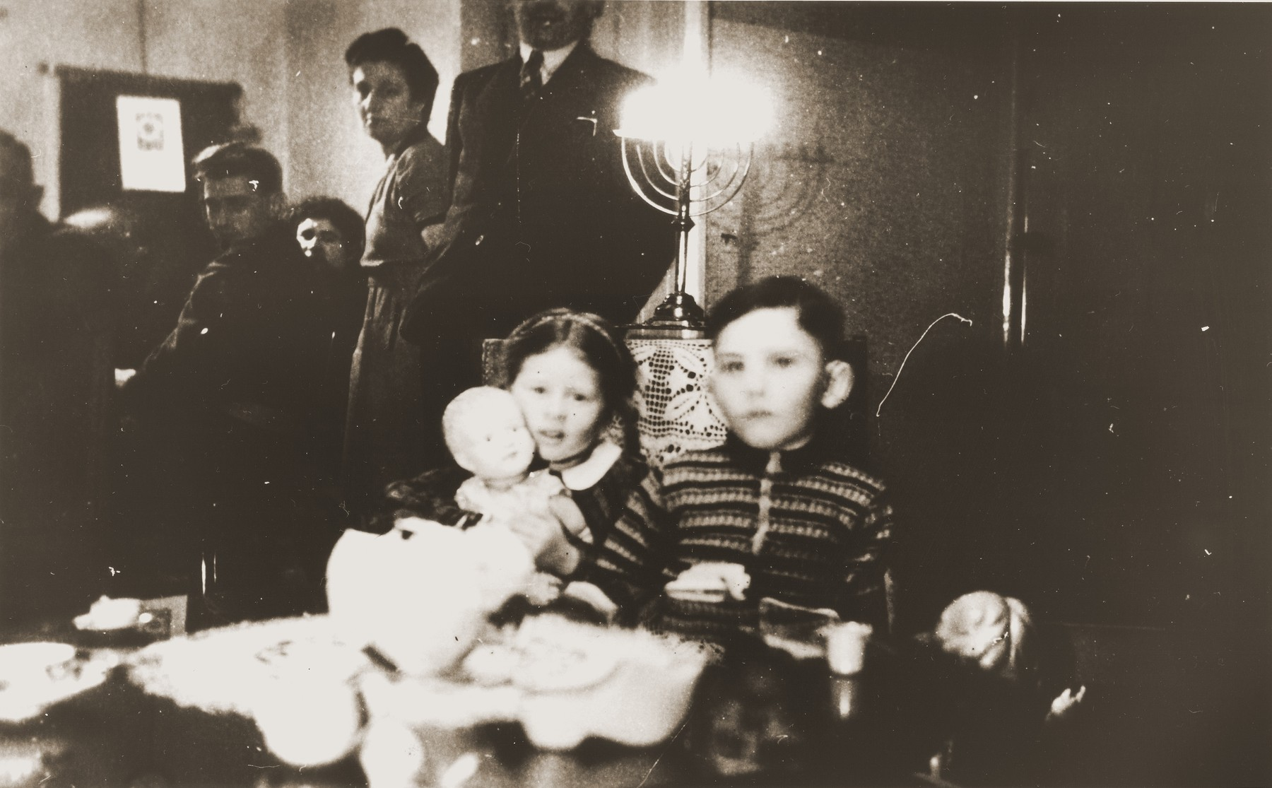 Two young Jewish children sit in front of a lighted Hanukkah menorah at the first postwar family Hanukkah celebration at the Zion home in Eibergen.  Pictured clutching her new doll is Betty Rosenbaum.  Betty, who was orphaned during the war, was adopted by her uncle Julius Zion after his marriage in 1946.