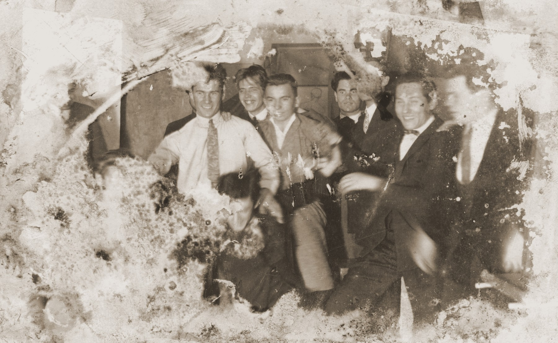 Damaged photograph of a group of male friends in Kovno, Lithuania that survived the destruction of the Kovno ghetto.  Among those pictured is the artist Jacob Lifschitz (center).  The photograph was buried with the artist's drawings shortly before the liquidation of the ghetto, and retrieved by his wife after the liberation.