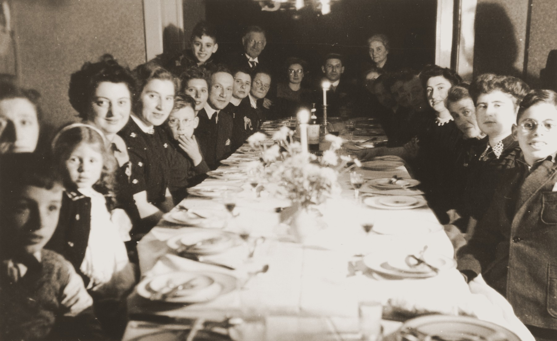 Engagement party for Julius Jacob Zion and Nora de Jong at the de Jong home in Enschede.  Among those pictured are the bride and groom (at the head of the table); the bride's father and mother (on either side of the bride and groom); Bep Meijer (fourth from the front on the right side); Frieda Zion (second from the front on the right side); and Betty Rosenbaum (the child second from the front on the left side).