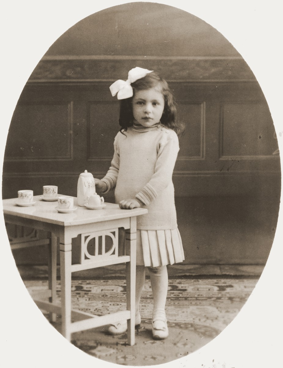 Studio portrait of Johanna Meijer playing with a tea set.    She perished along with her three siblings during the Holocaust.