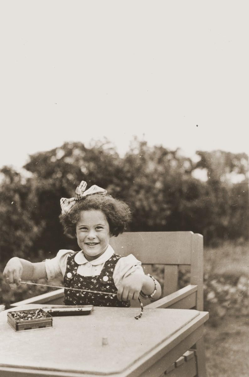 Hanneke (Hanna Jetty) Leijdesdorff strings beads at her Great Aunt Hennie Meijer's house in Boekelo.  Hanneke survived the war in hiding.