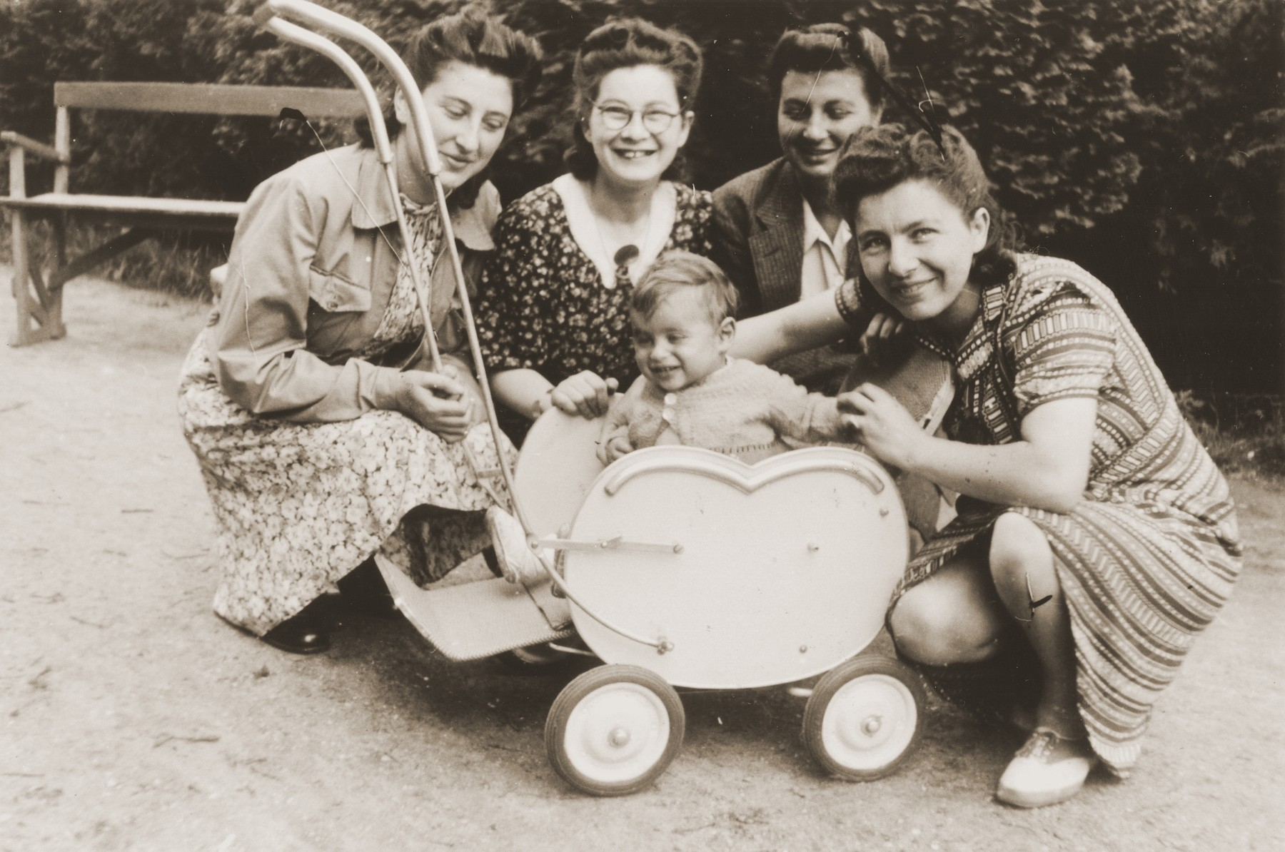 A young Jewish child sits in a stroller in a park surrounded by his mother (right) and three aunts.  Pictured is the toddler, Rene Gruneberg; his mother, Bertha Gruneberg; and his aunts (left to right): Bep Meyer; Bettie Meijer, and Renee (Sara) Meijer.  The child survived the war, but both his parents were killed.